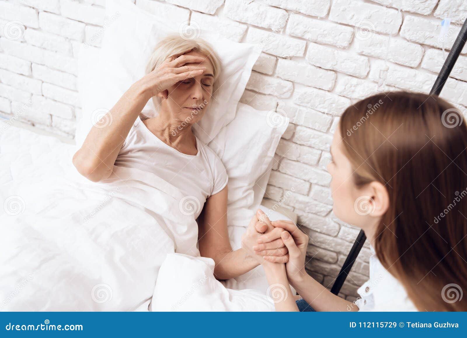 La fille soigne la femme agée à la maison Elles tiennent des mains La femme se sent mal