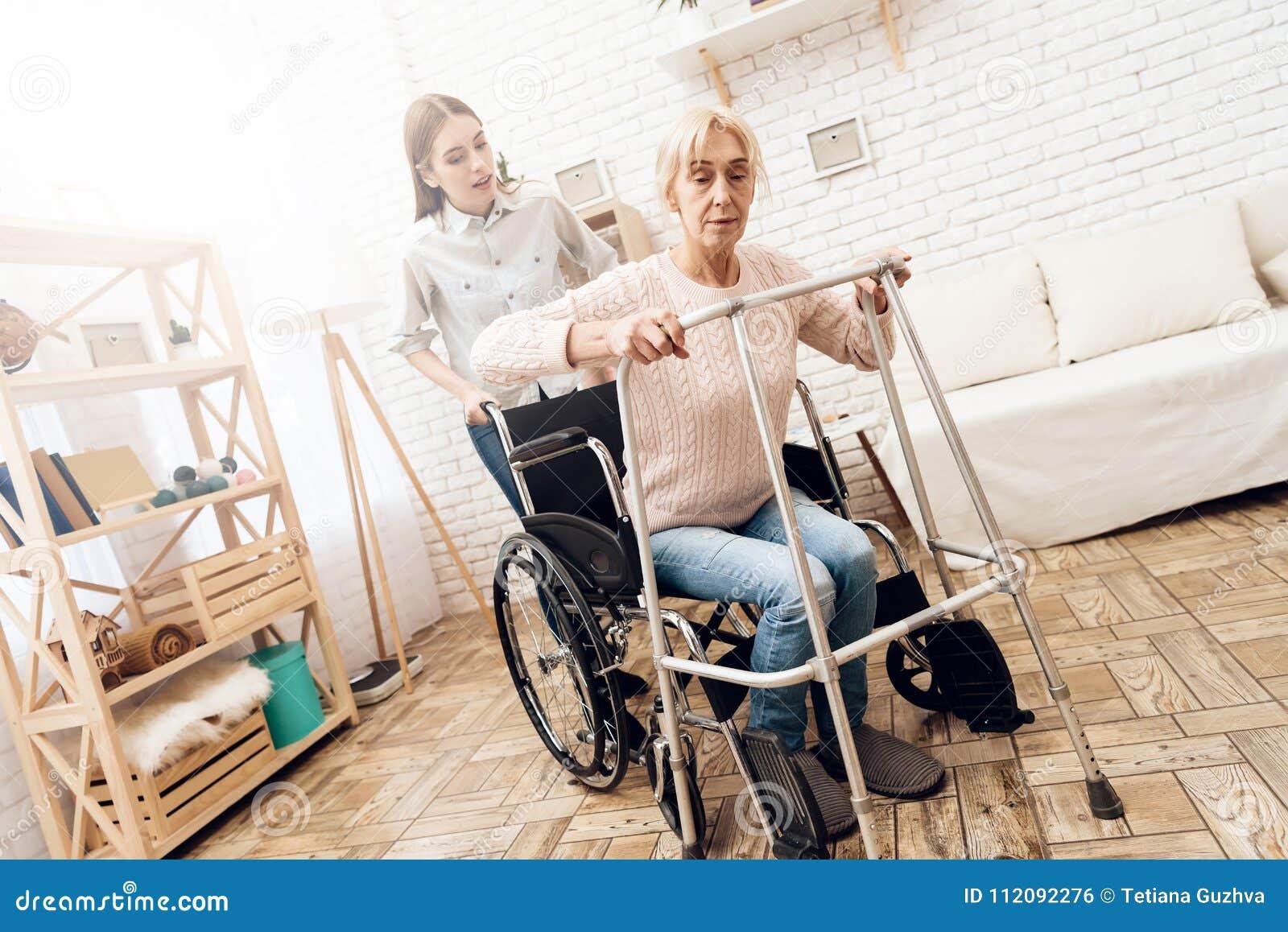 La fille soigne la femme agée à la maison La femme essaye de se lever du fauteuil roulant