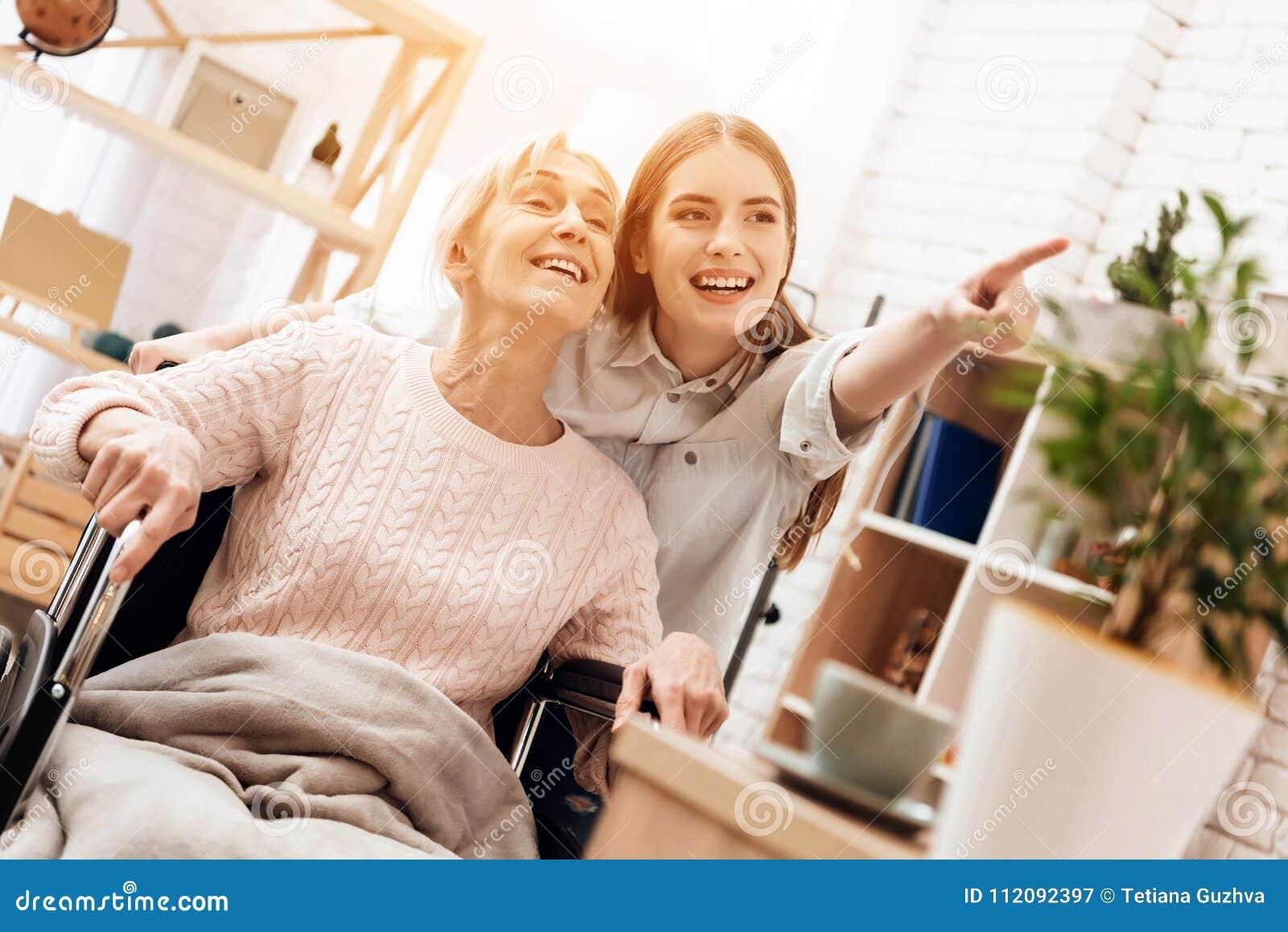 La fille soigne la femme agée à la maison La fille monte la femme dans le fauteuil roulant dans le salon