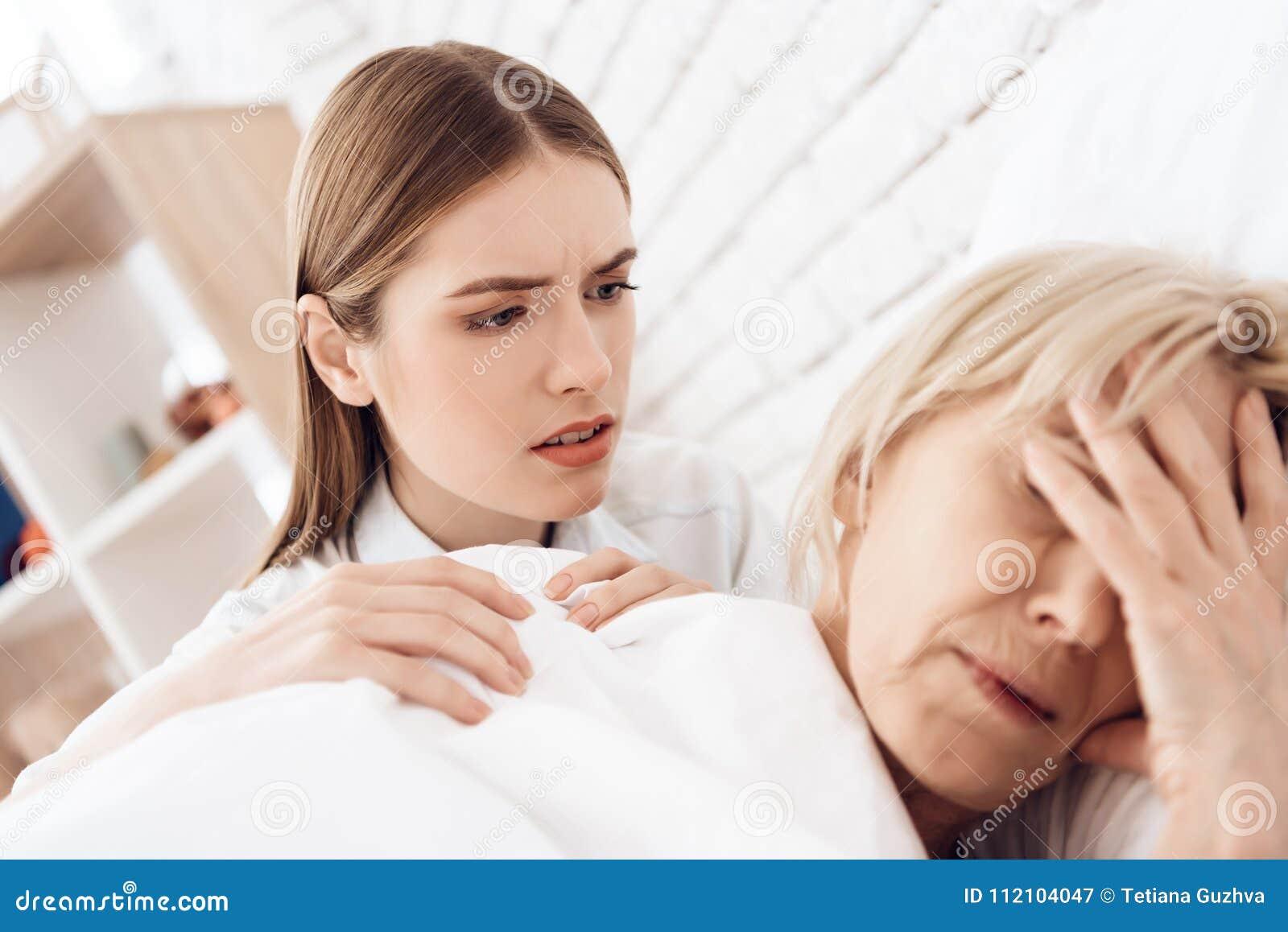 La fille soigne la femme agée à la maison La femme se sent mal, fille est concernée
