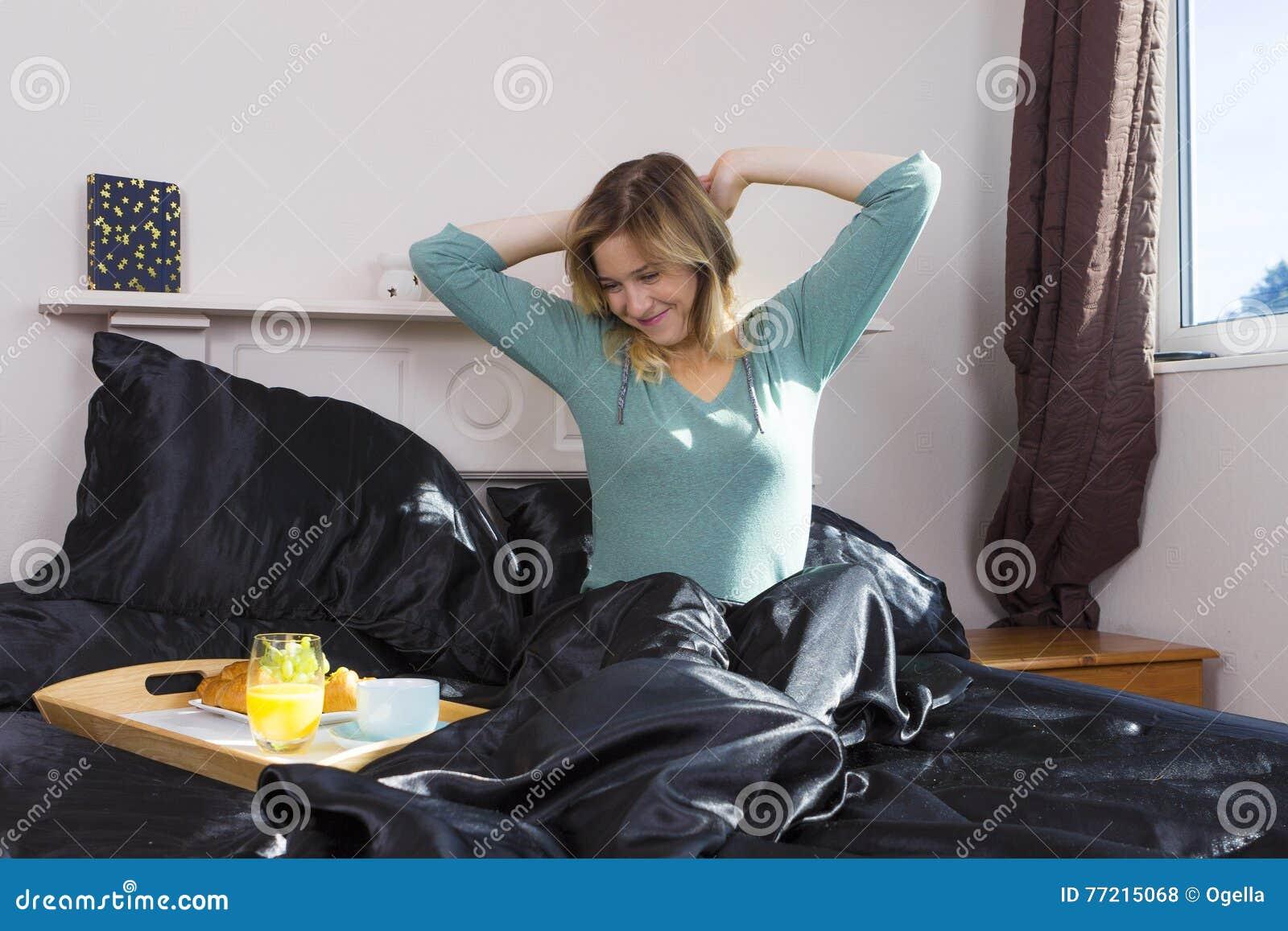 La fille stratching dans la chambre à coucher se réveillent
