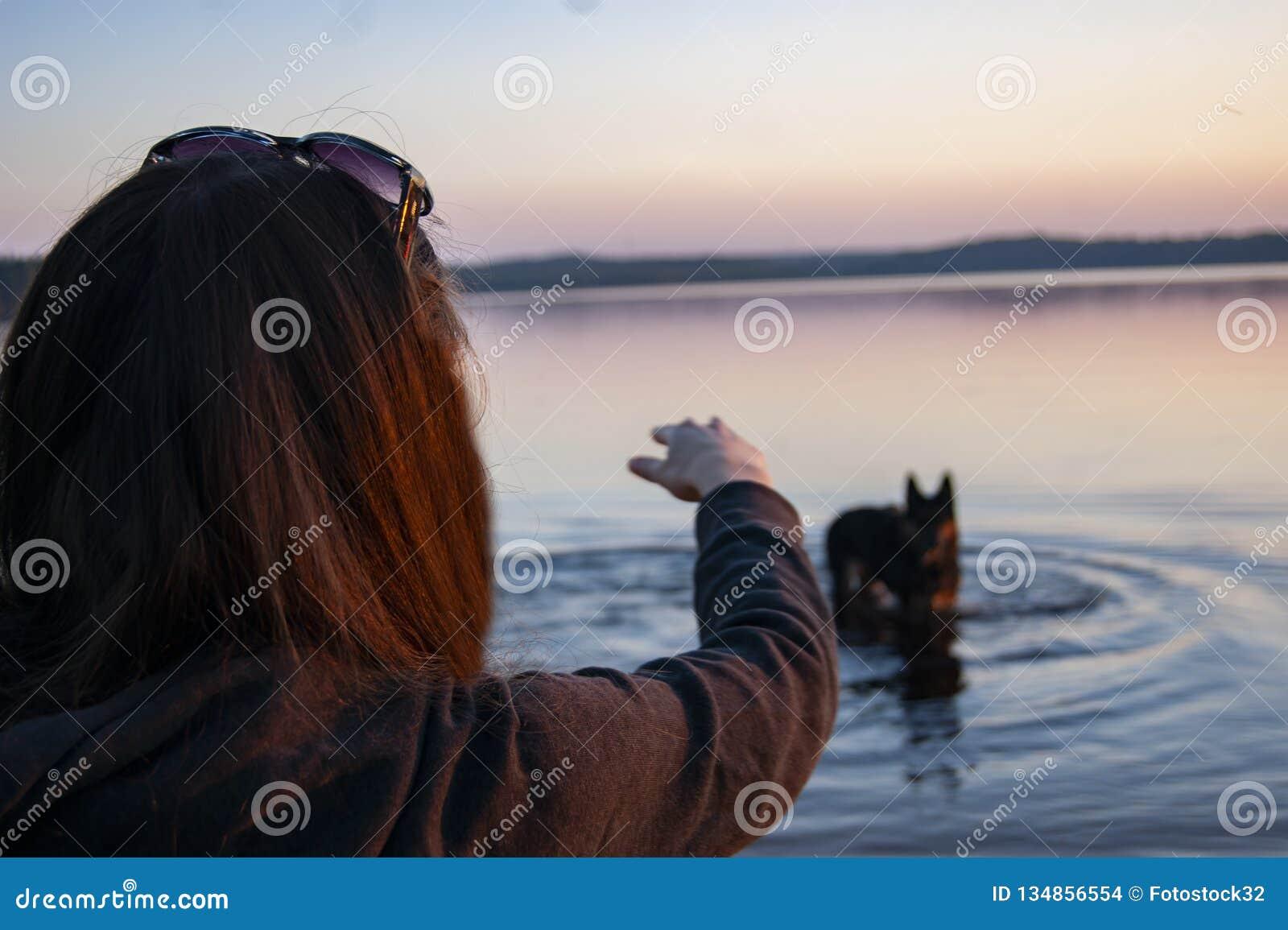 La fille sur le lac jouant avec un chien