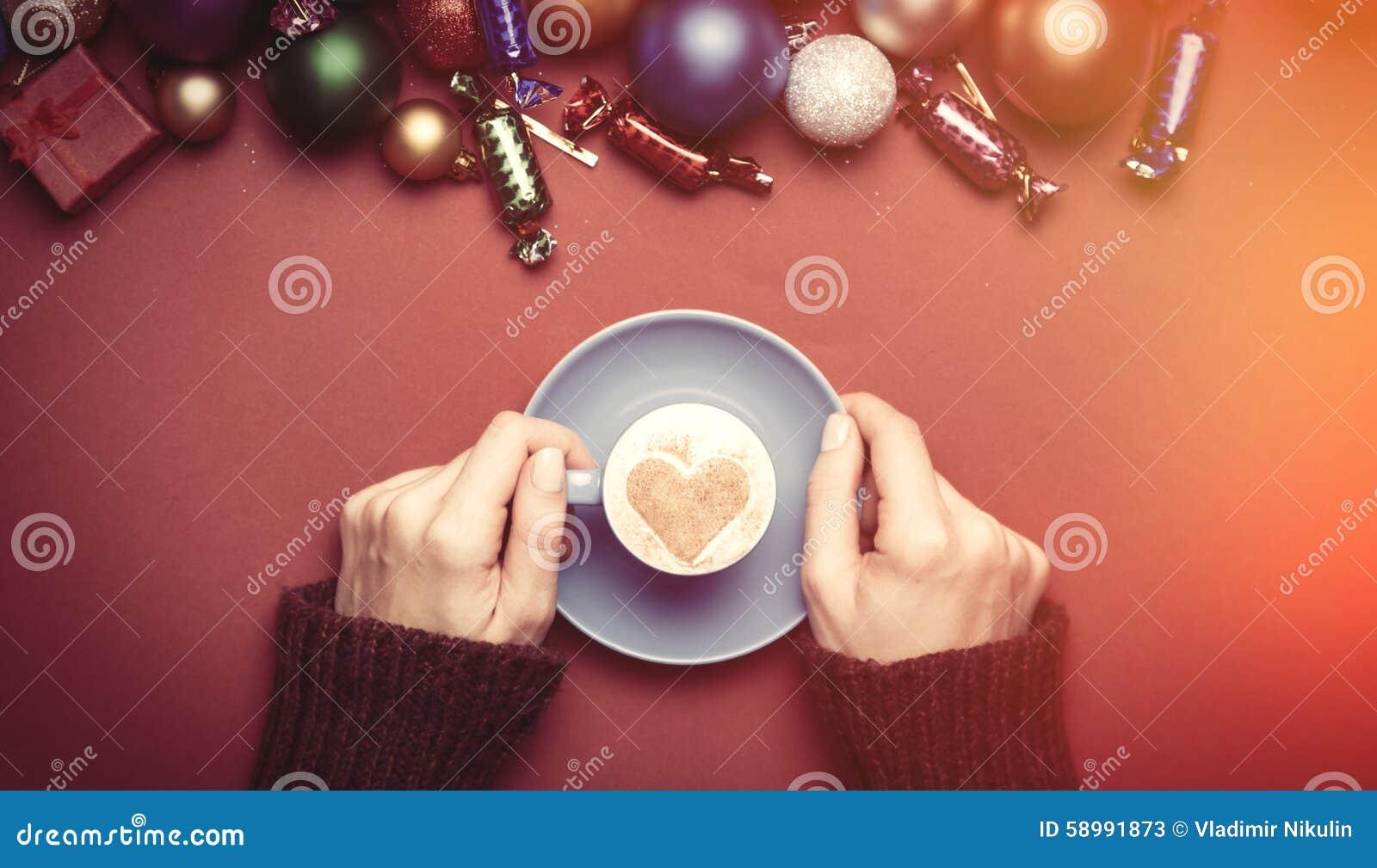 La fille tenant la tasse de café près de Noël joue