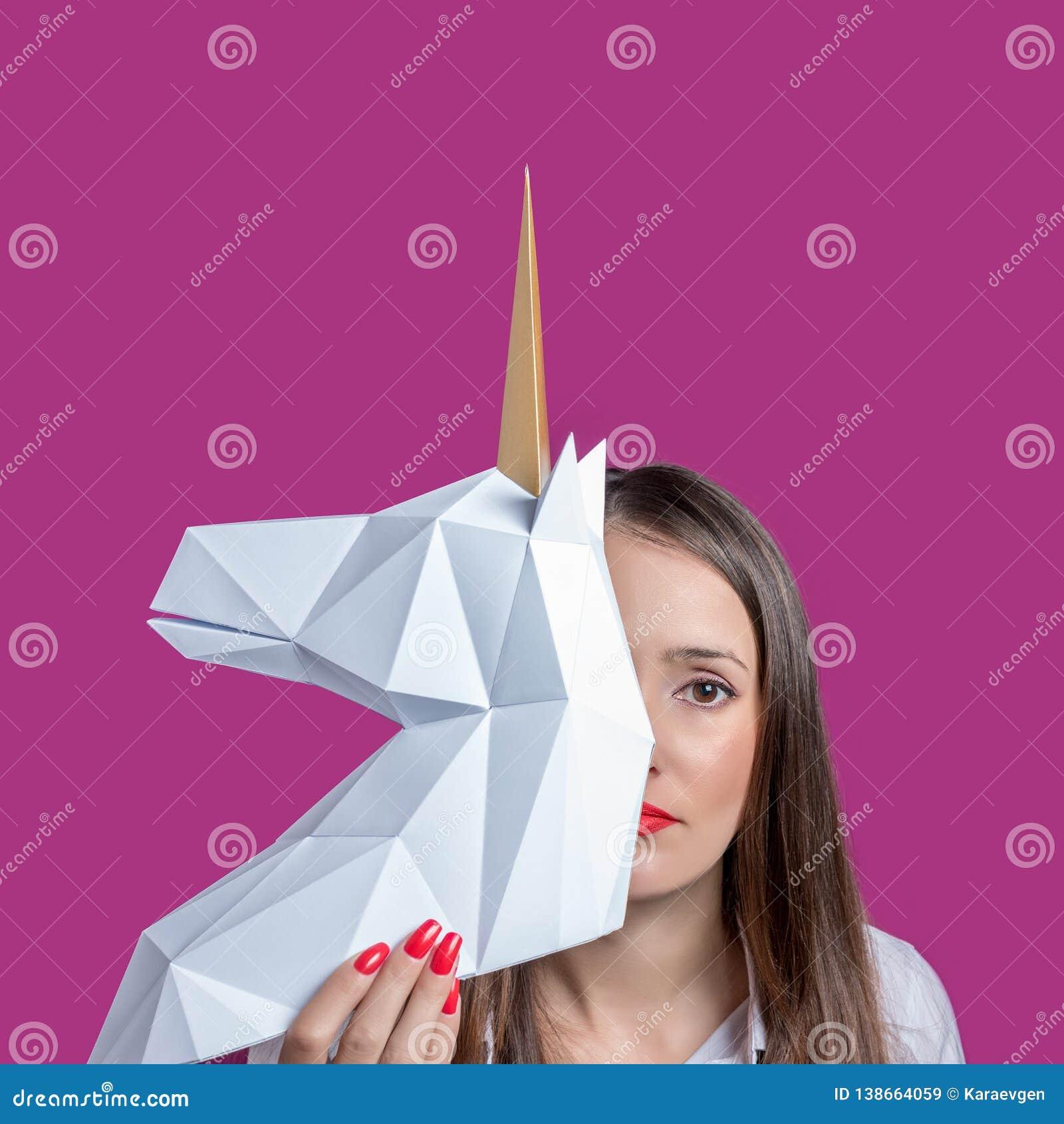 La fille tient un modèle blanc du papercraft 3d de licorne Art Concept minimal