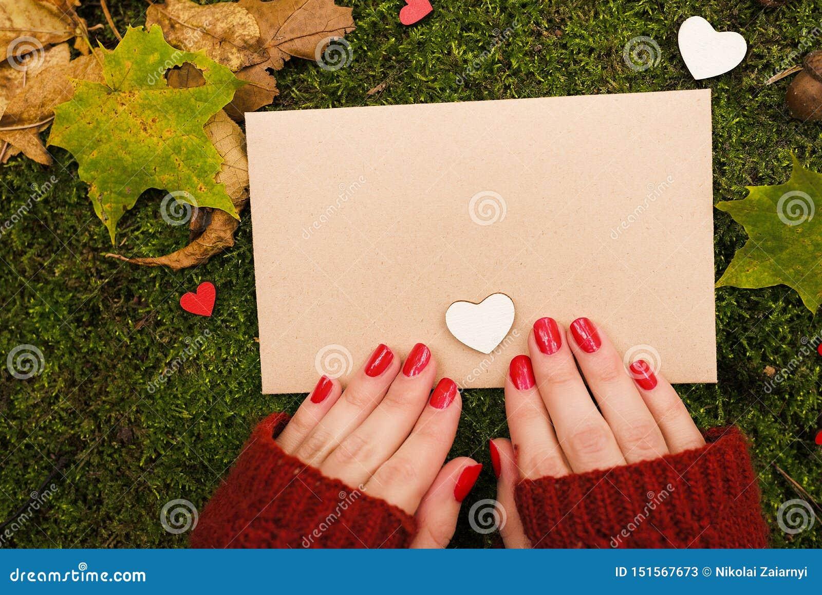 La fille tient une feuille de cru de papier en parc d automne