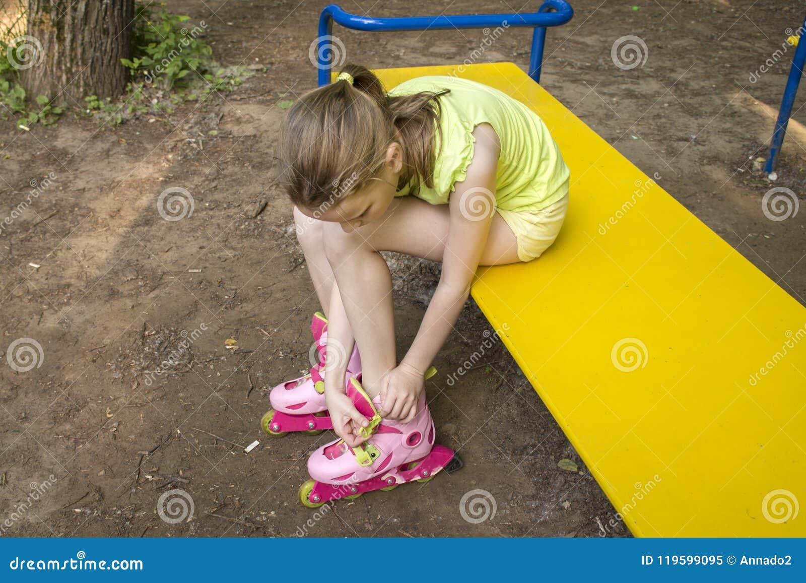 La fille vêtx des rouleaux se reposant sur un banc de parc