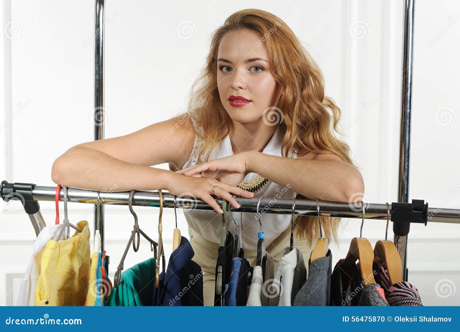 La fille vend des vêtements accrochés sur des cintres