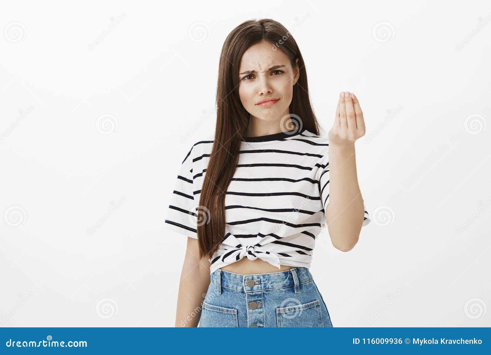 La fille veut l acte minuscule du respect Femme européenne interrogée mécontente avec les cheveux bruns, fronçant les sourcils de