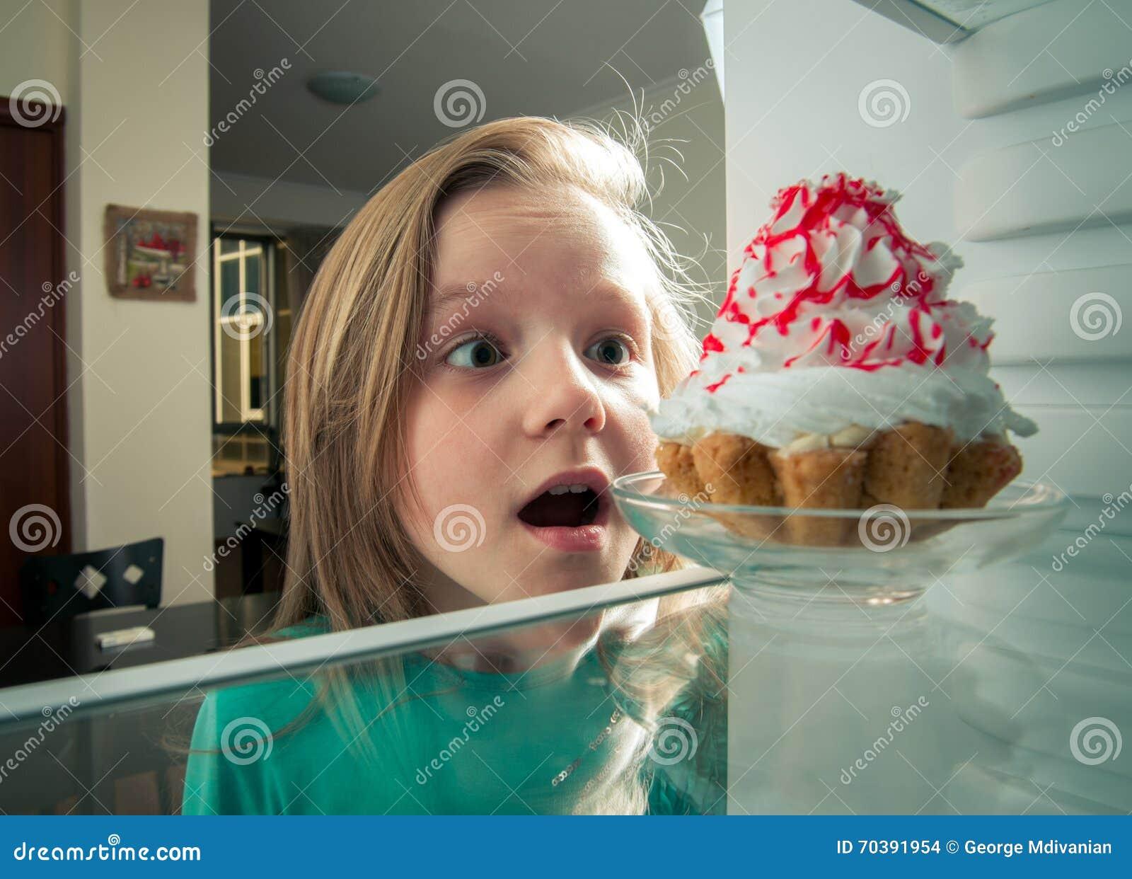 La fille voit le gâteau doux le réfrigérateur