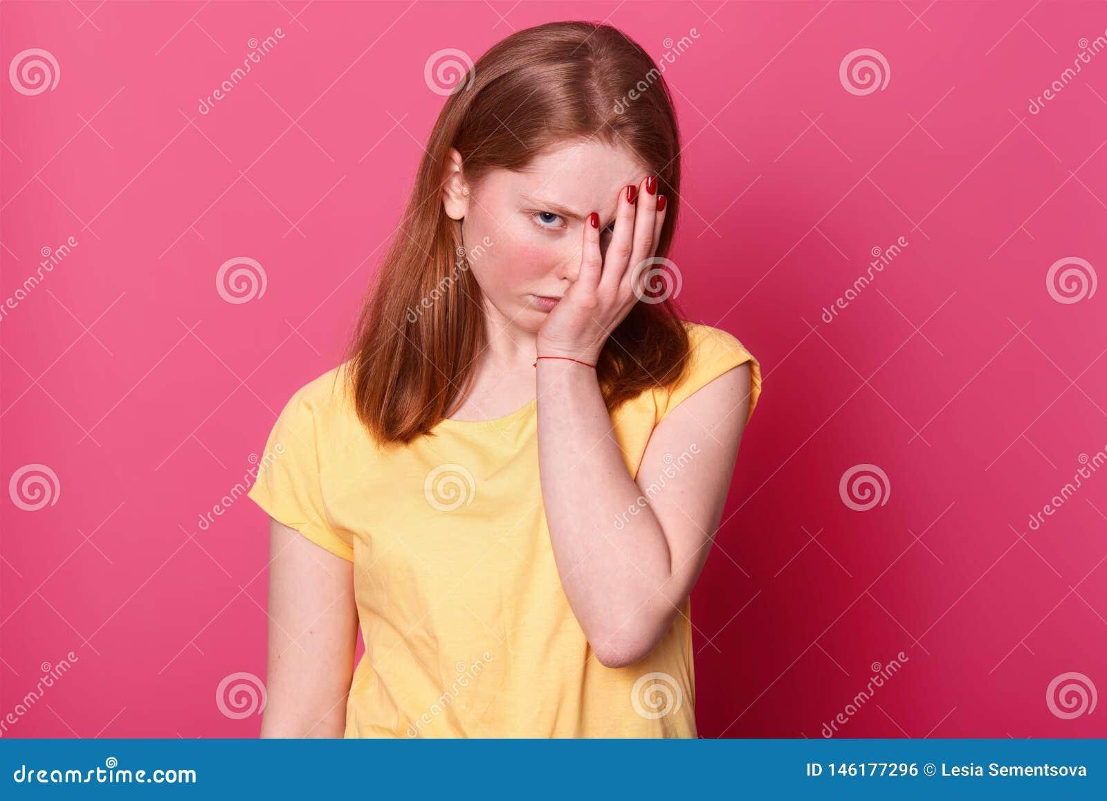 La fin du portrait haut de la jeune belle femelle d étudiant, couvre le visage de main, étant fatigué après école, a un bon nombr