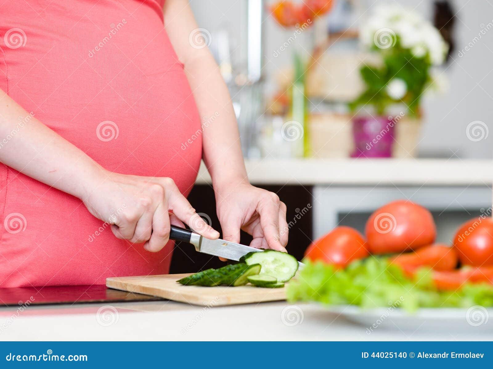 La fin vers le haut de la femme enceinte avec le couteau sur la cuisine coupe le concombre