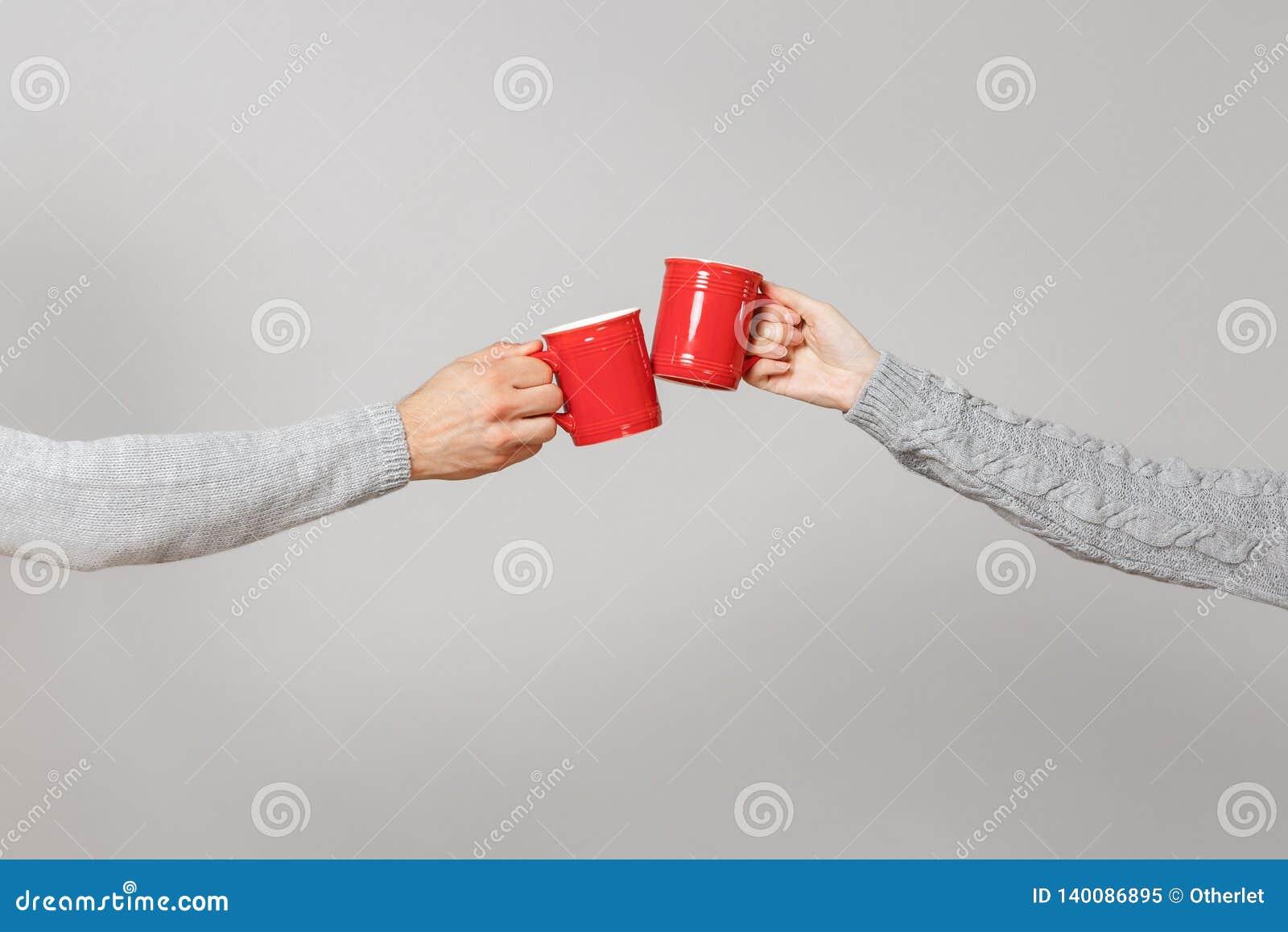 La fine su ha potato della donna, orizzontale delle mani dell uomo due che tiene le tazze rosse di tè, tintinnio isolato sul fond