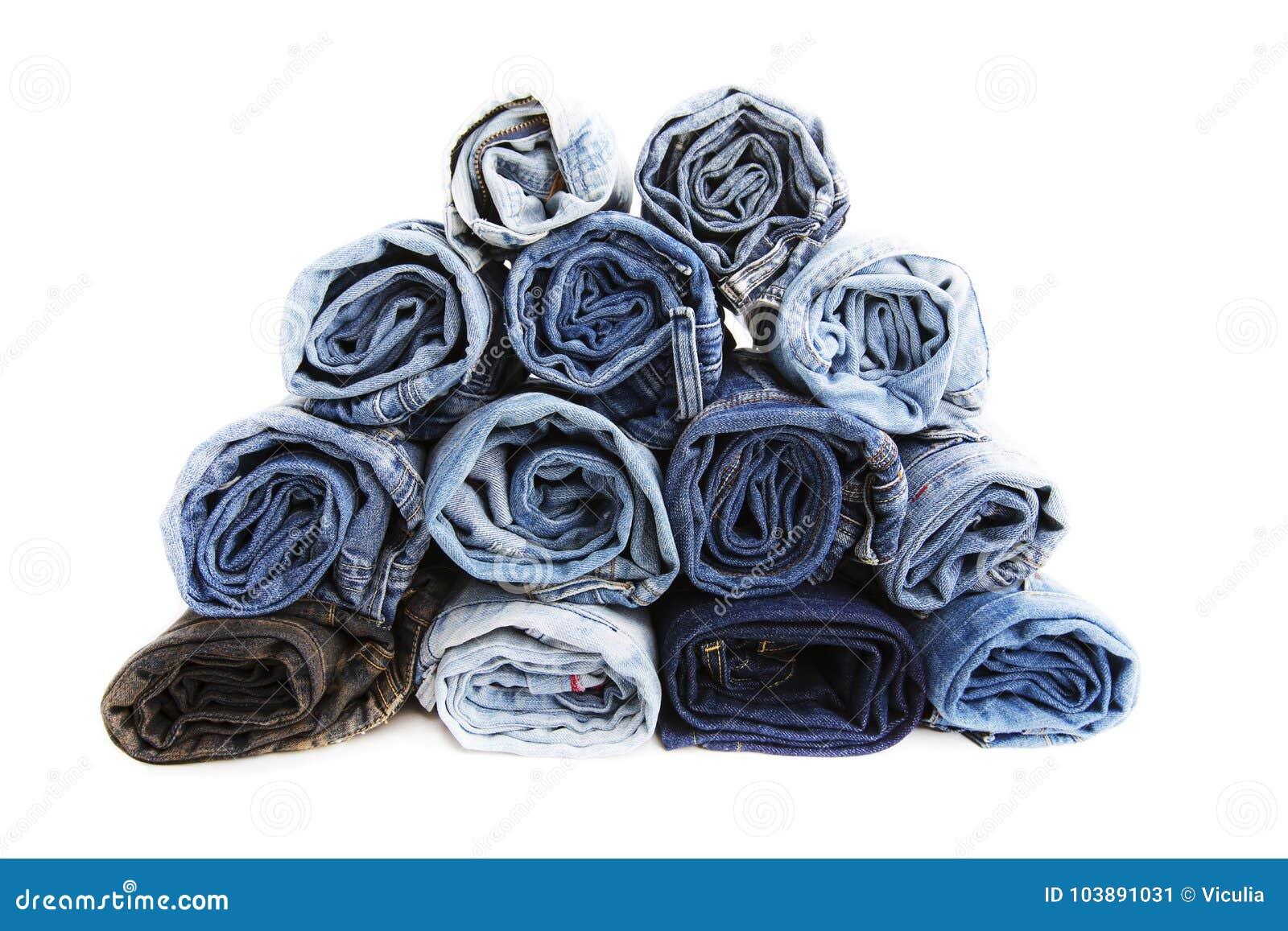 La fine su ha rotolato dei pantaloni delle blue jeans, pantaloni blu scuro del denim che mostrano la struttura