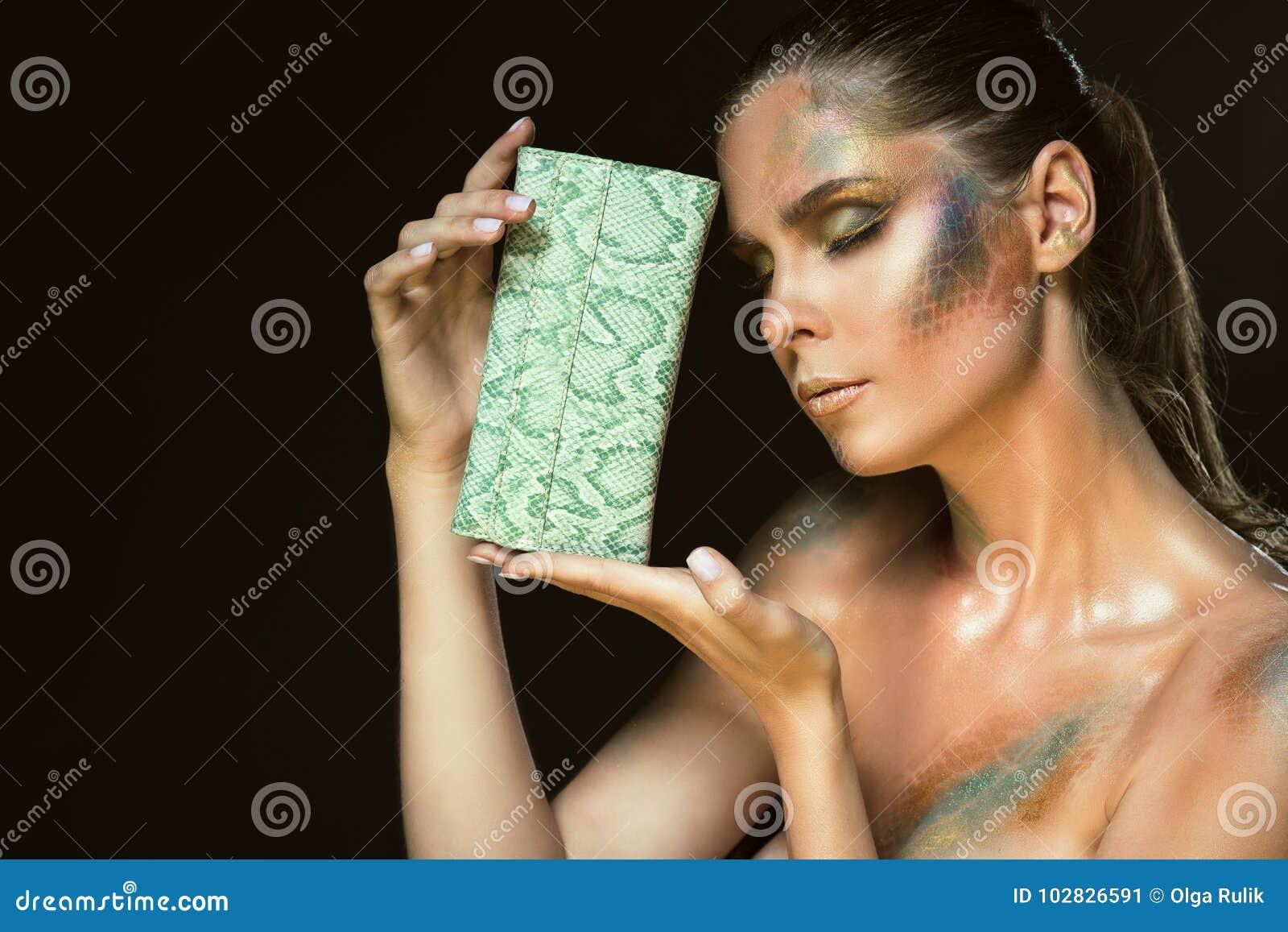 La fine sul ritratto della donna splendida con gli occhi chiusi e lo snakeskin artistico compongono la tenuta della borsa di cuoi