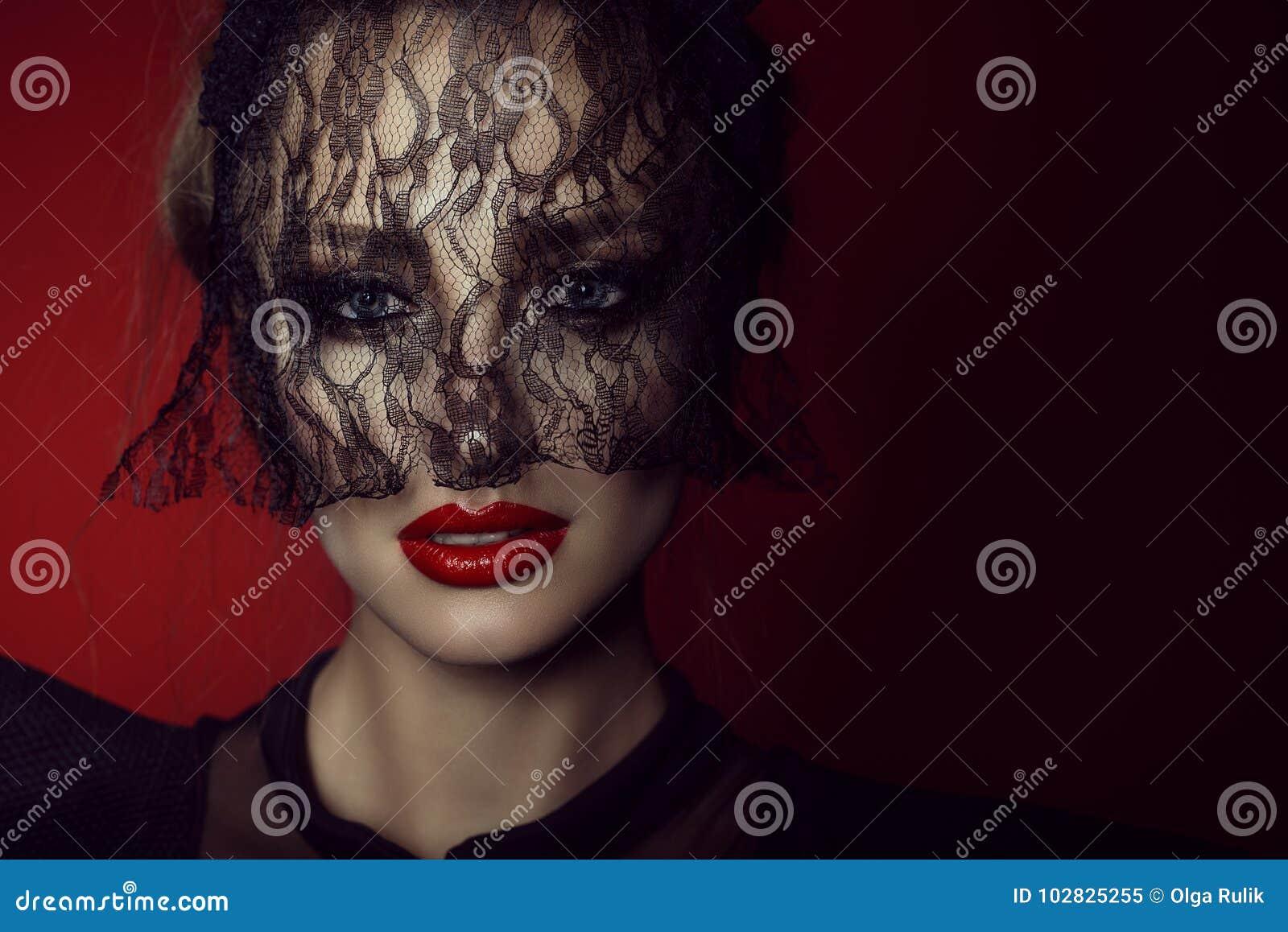 La fine sul ritratto di bella signora con gli occhi azzurri vivi e perfetti compongono nascondere il suo fronte dietro il velo de