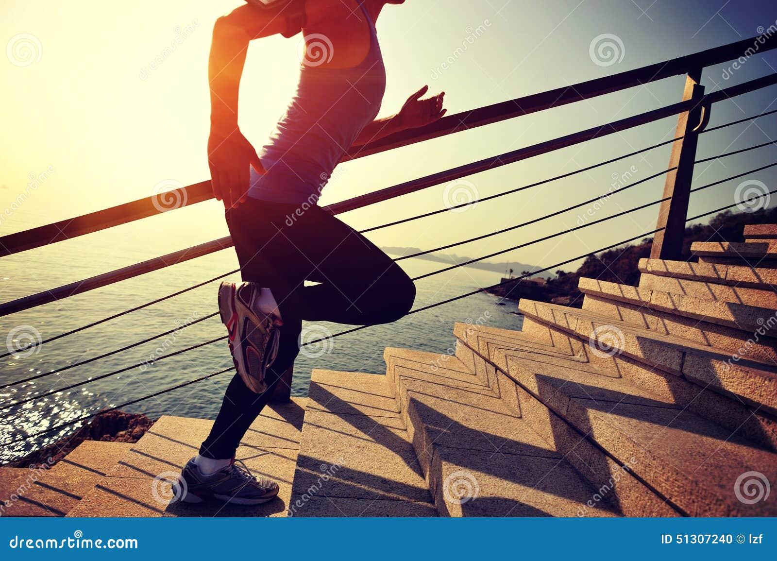 La forma de vida sana se divierte a la mujer que corre para arriba en la salida del sol de piedra de las escaleras