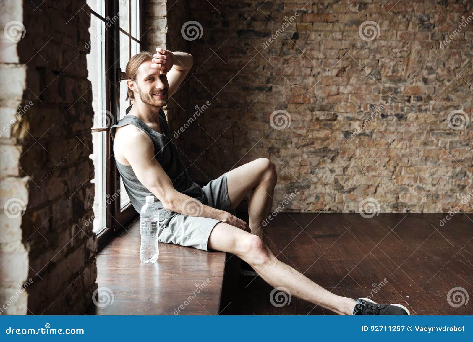 La forme physique de sourire équipent le repos au rebord de fenêtre avec la bouteille d eau