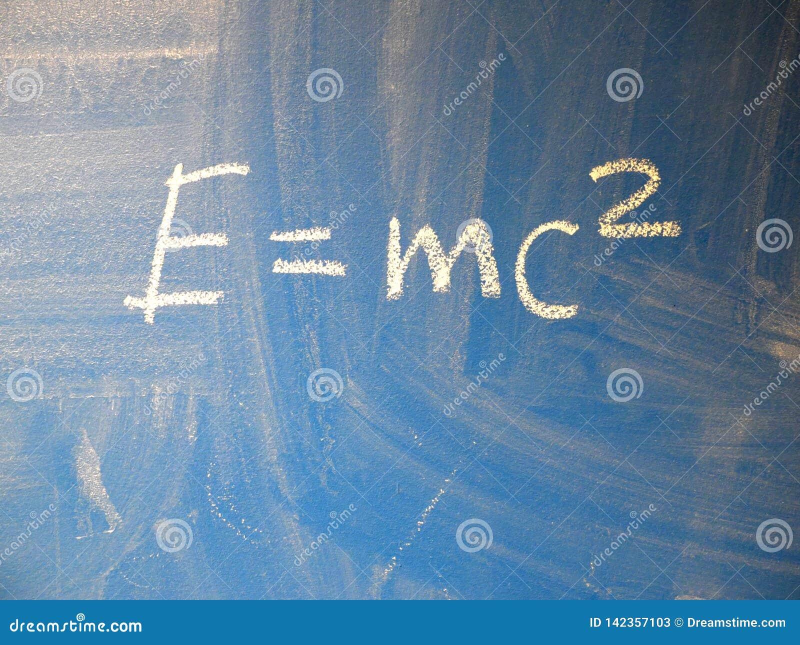 La formule mathématique e=mc2 a ajusté écrit sur un tableau bleu et relativement sale par la craie