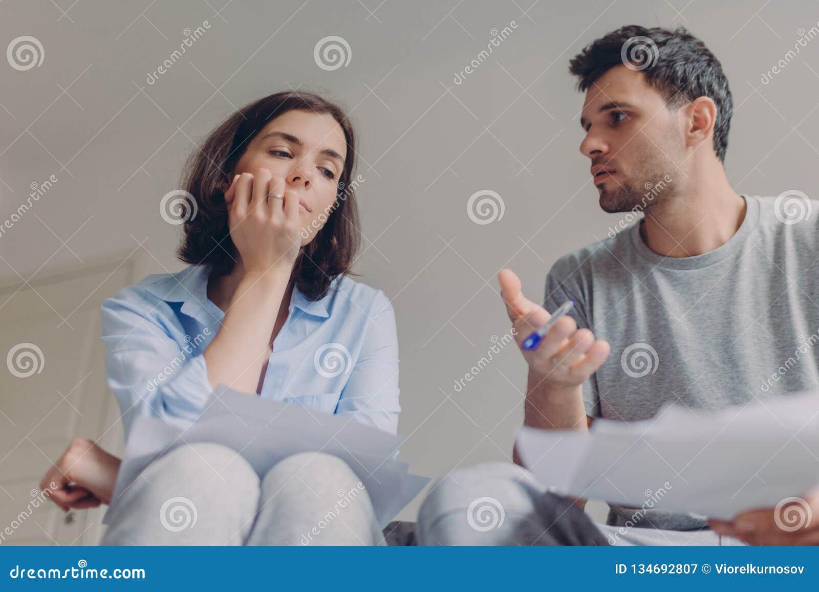 La foto de femenino y masculino serios hacer papeleo juntos, documentos del banco del estudio y sostener la pluma, discutir algo,