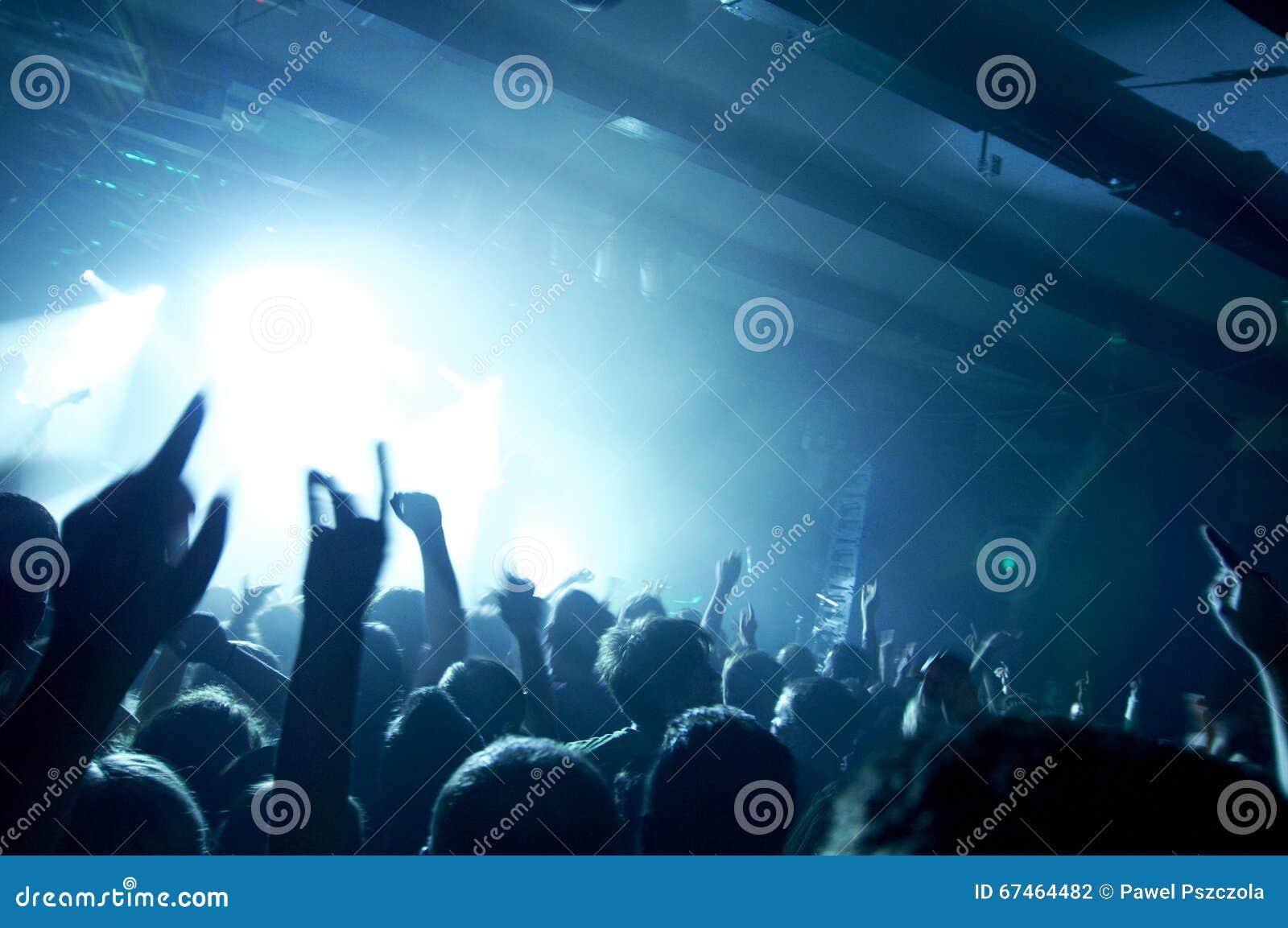 La foto de la gente que se divierte en el concierto de rock, fans que aplauden a la música famosa congriega, estrella del rock en
