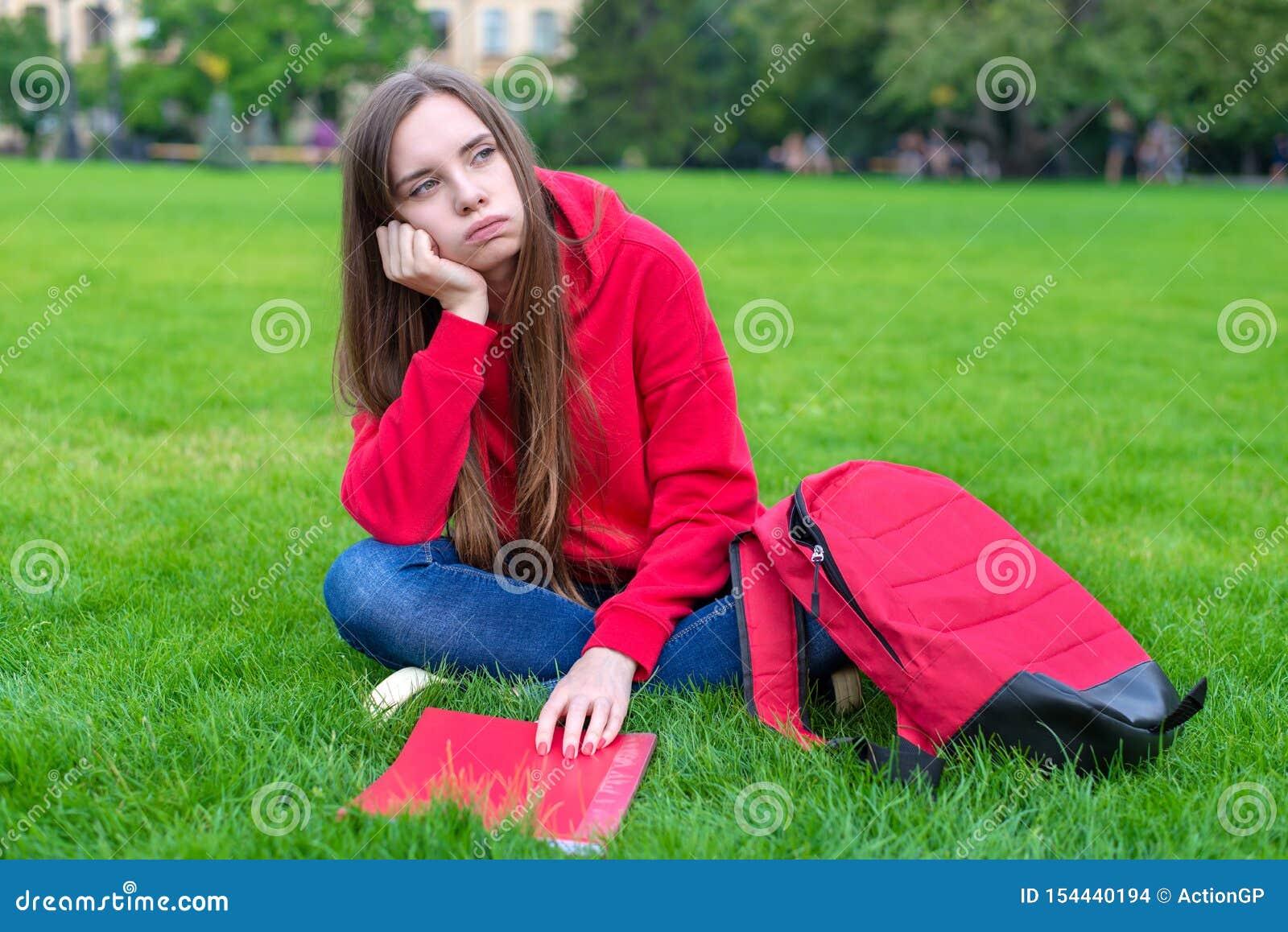 La foto de la muchacha adolescente triste pasiva deprimida que se sienta en césped de la hierba verde no está dispuesta a hacer l