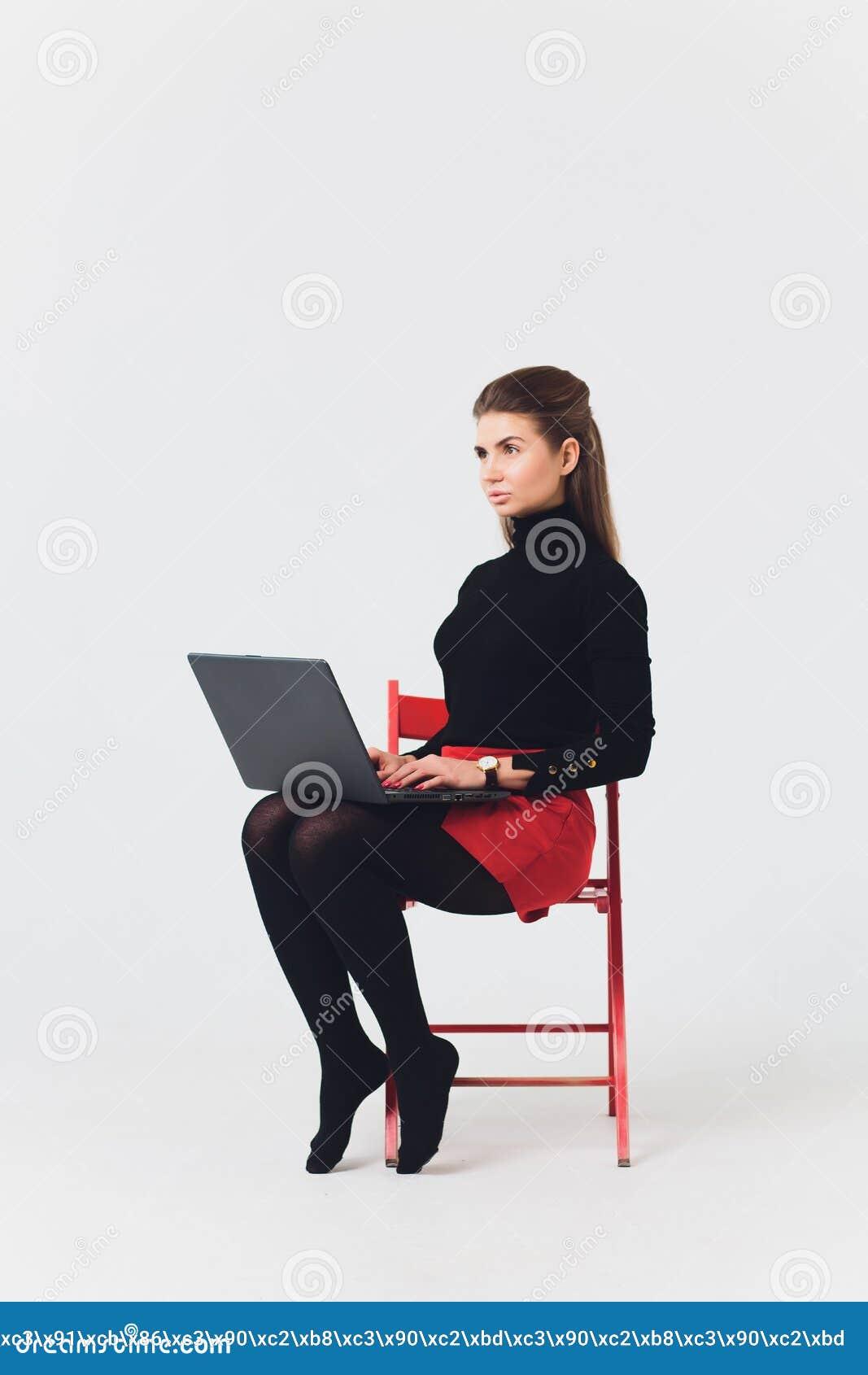 La foto de la mujer hermosa 20s que sonreía y que usaba el ordenador con las piernas cruzó aislado sobre el fondo blanco