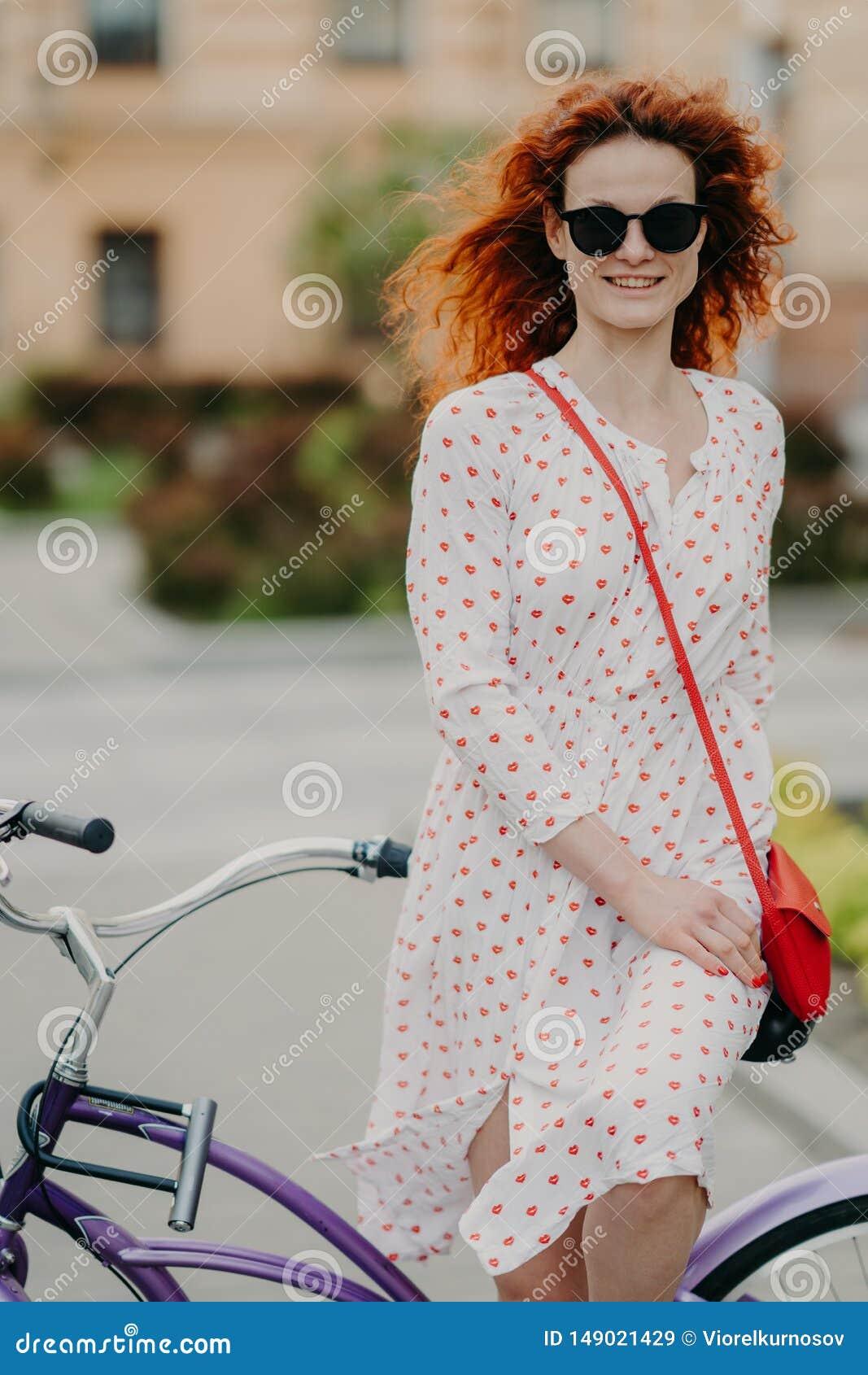 La foto de la mujer pelirroja alegre con sonrisa apacible, gasta la bicicleta del montar a caballo del tiempo libre en calles de