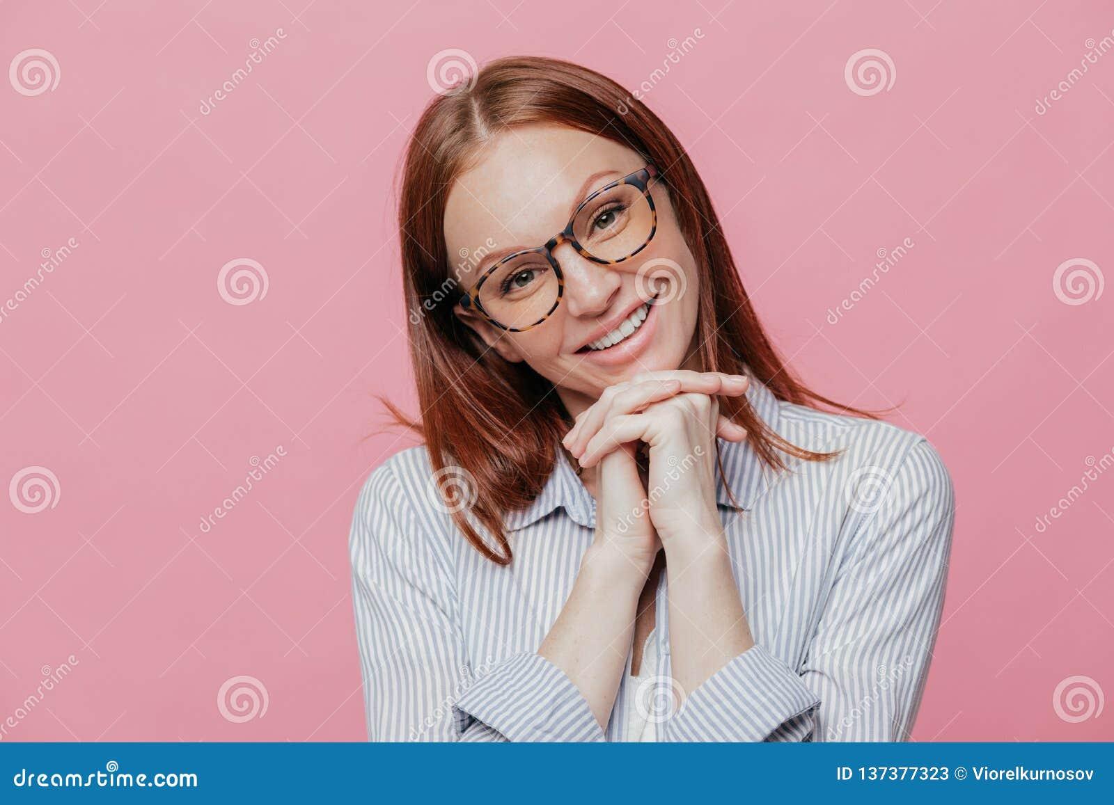 La foto de la mujer satisfecha inclina la cabeza, guarda las manos juntas debajo de la barbilla, tiene pelo marrón, lleva la cami