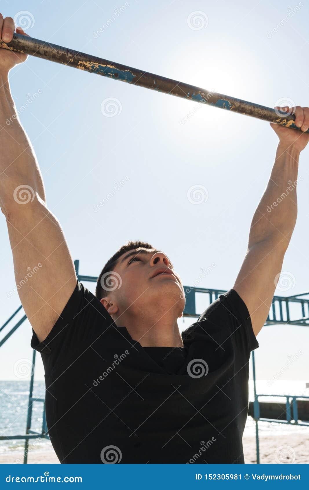 La foto del hombre muscular que hace tirón sube en barra gimnástica horizontal durante entrenamiento de la mañana por la playa