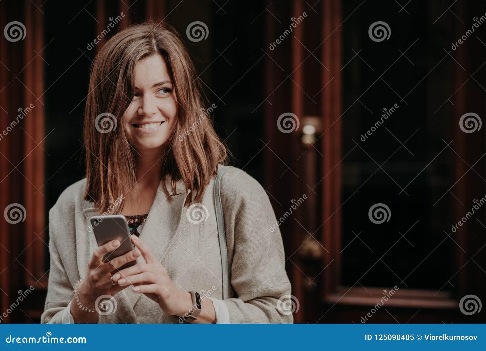 La foto di bella donna cerca le informazioni, utilizza il telefono cellulare, vestito in rivestimento elegante, pose contro il fo