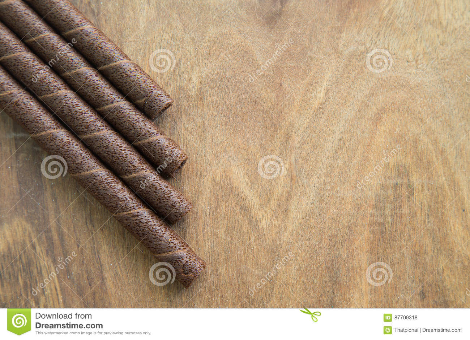 La gaufrette roule avec du chocolat sur la table en bois