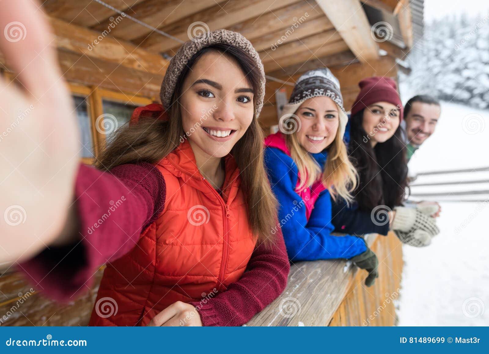 La gente agrupa tomar a foto de Selfie el teléfono elegante centro turístico de montaña de madera de la nieve del invierno de la
