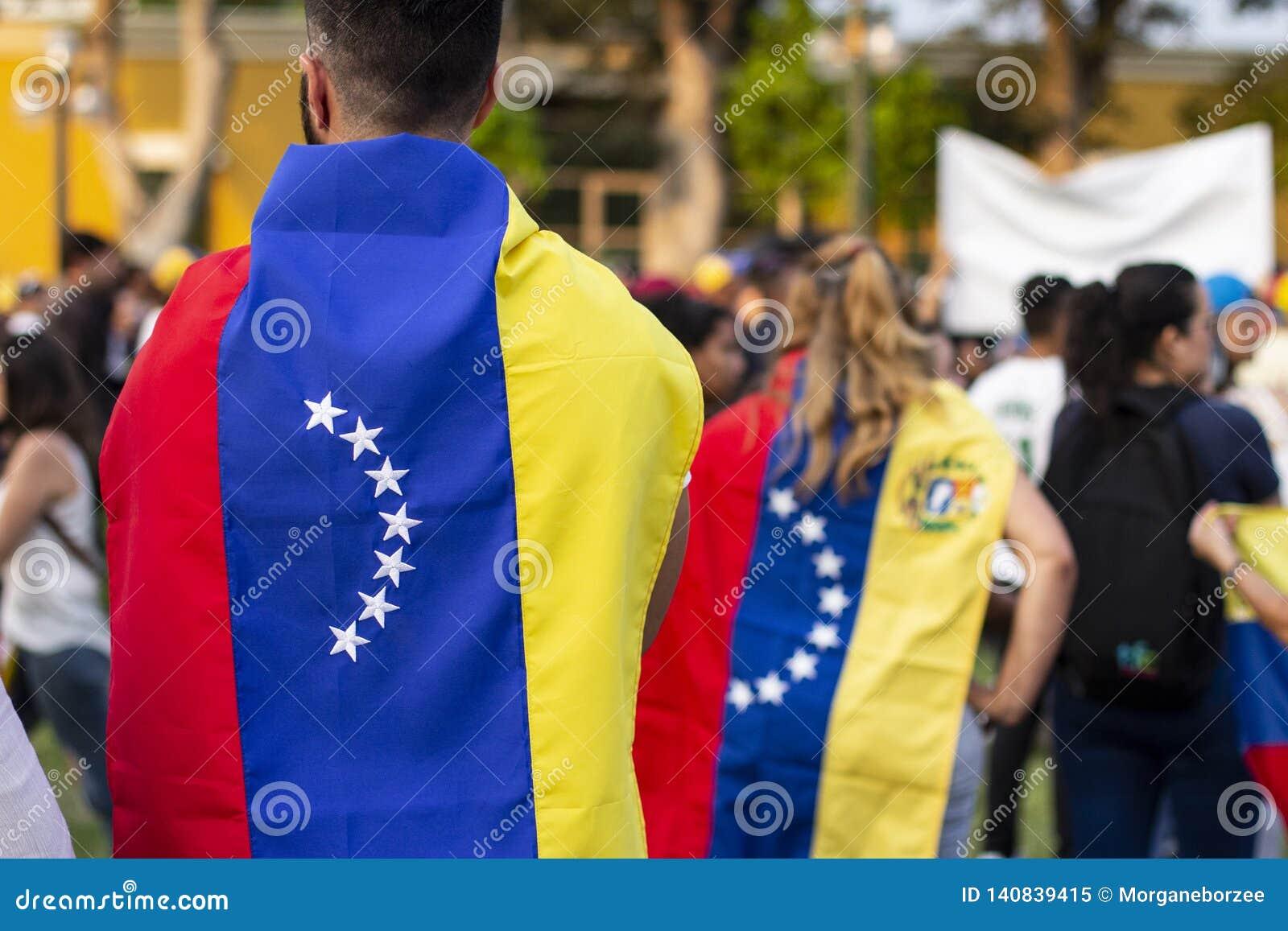 La gente avvolta in bandiere venezuelane alla protesta