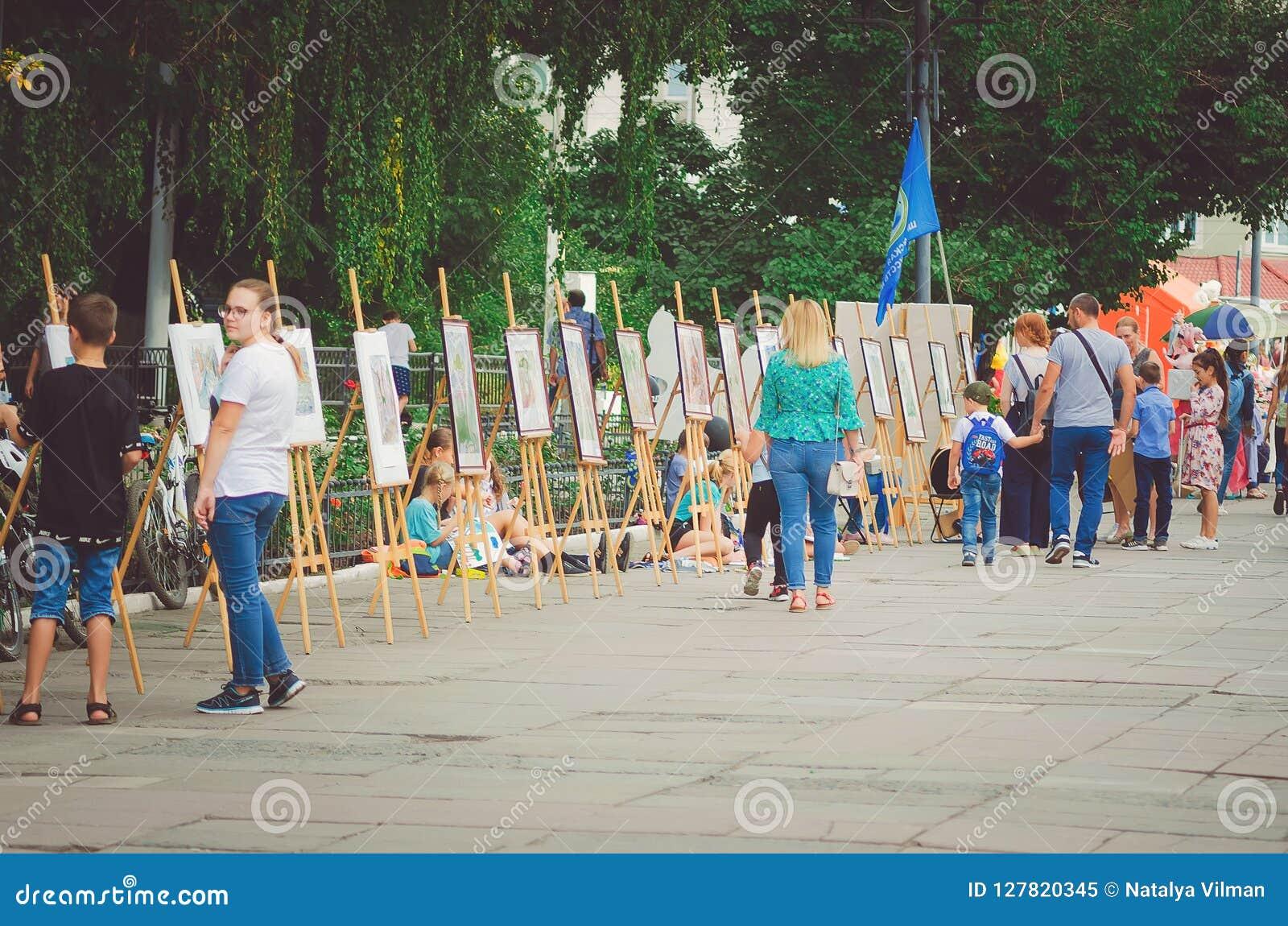 La gente camina en el parque en la celebración del día del ` s de la ciudad y mira la exposición del PA