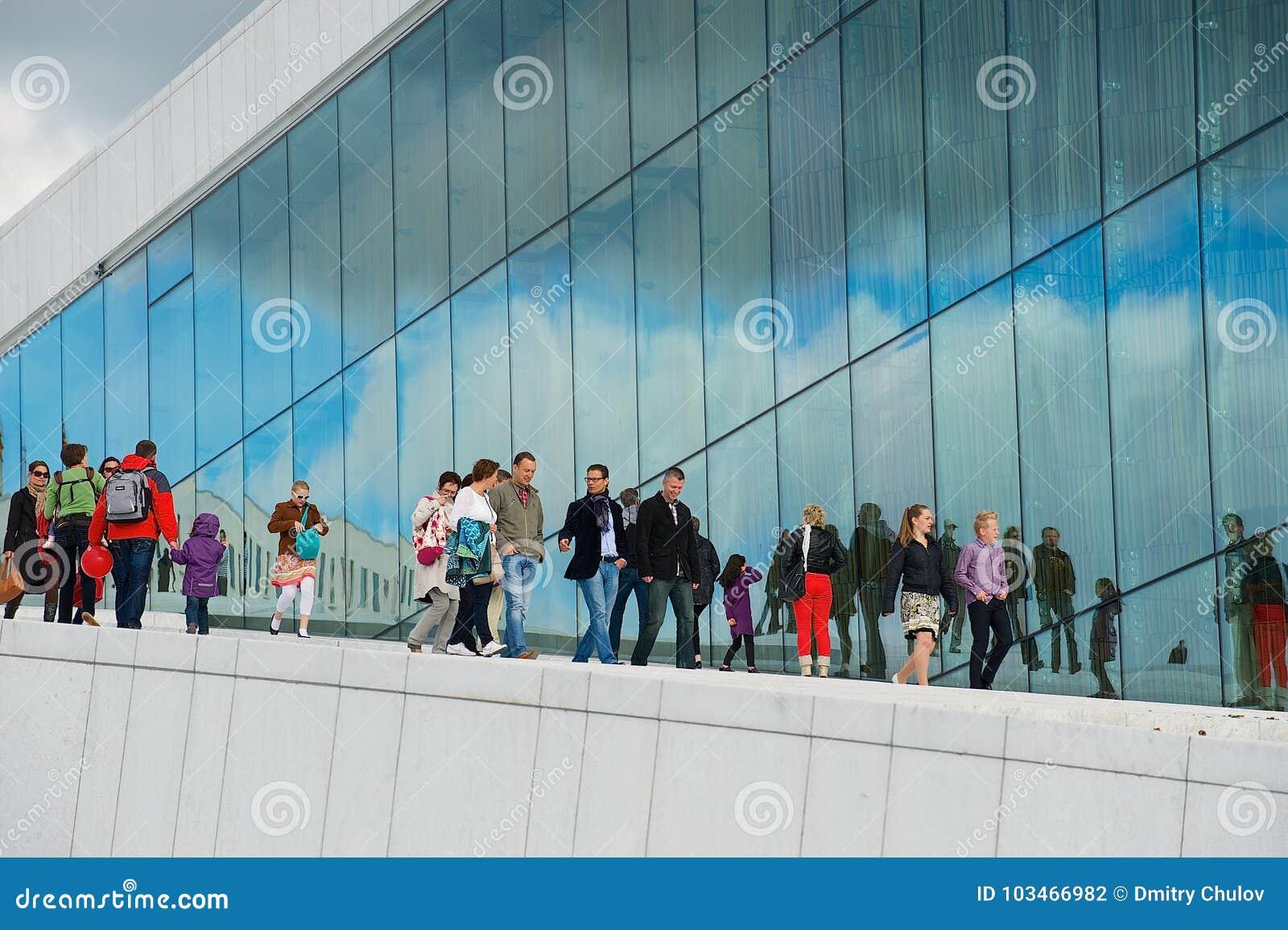 La gente cammina dalla parete laterale della costruzione di teatro dell opera nazionale di Oslo a Oslo, Norvegia