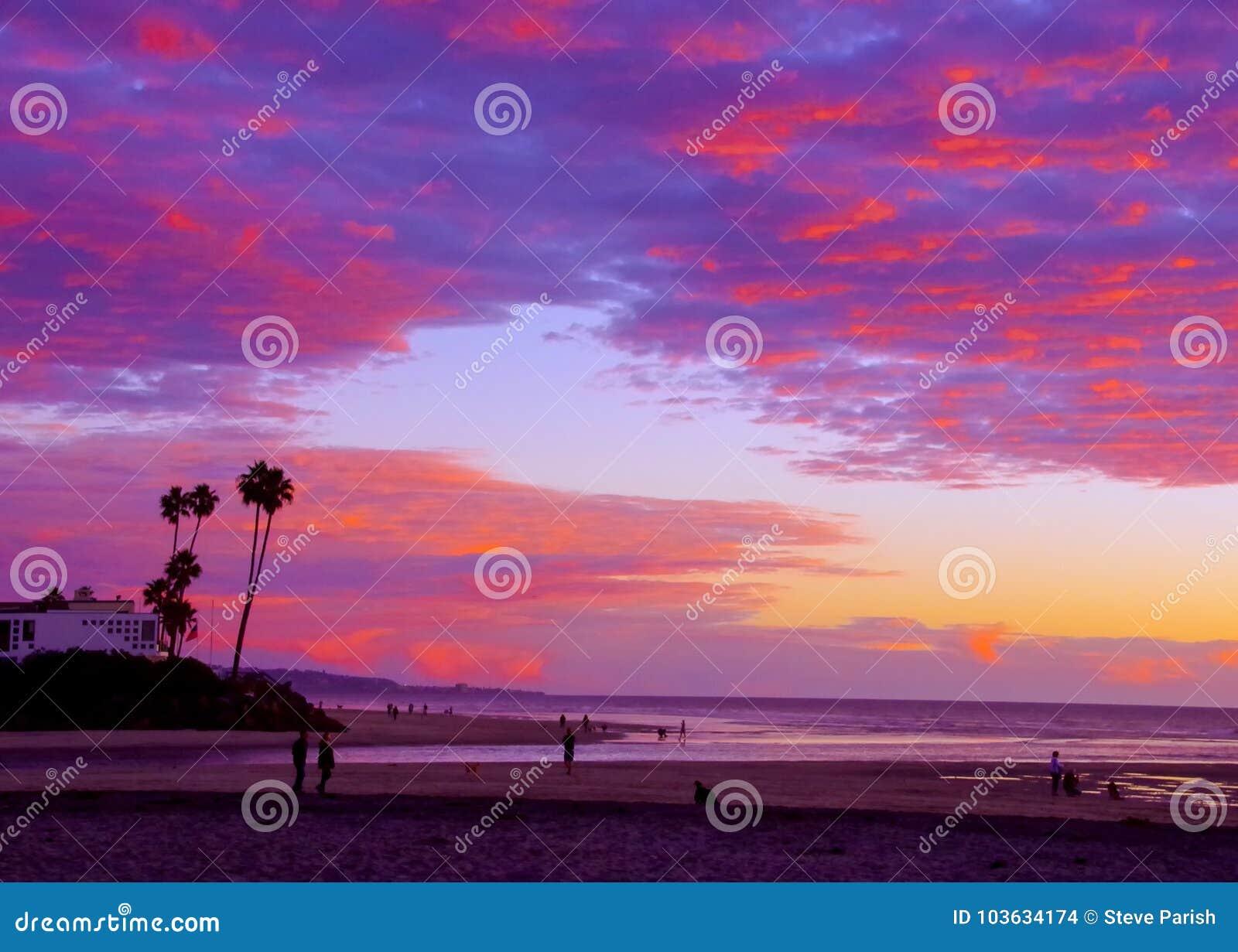 La gente cammina lungo la spiaggia con l entrata di marea che gode di un tramonto glorioso, Del Mar, la California