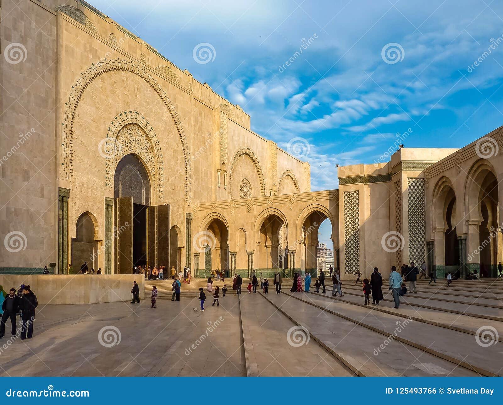 La gente che cammina vicino ai portoni decorati della moschea Hassan II Casablanca, Marocco