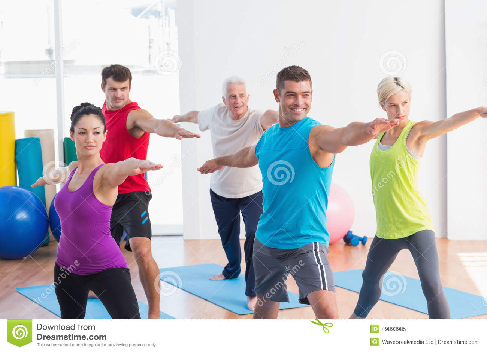 La gente che fa posa del guerriero nella classe di yoga