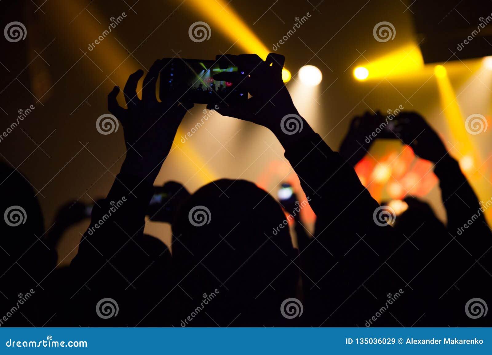 La gente che guarda un concerto e qualcuno foto e video della fucilazione con un cellulare