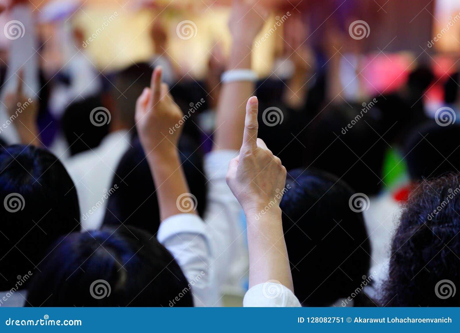 La gente che reagisce alla domanda alzando il loro dito indice insieme come lavoro di squadra per unità ed accordo e collabora un