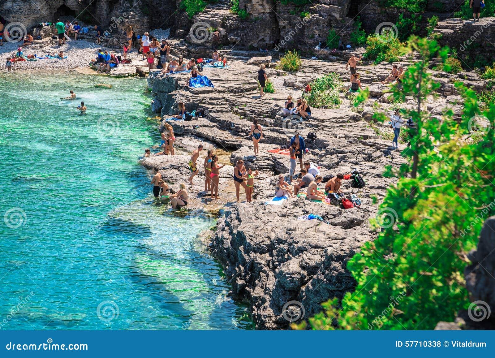 La gente che si rilassa alla bella spiaggia rocciosa d - Alla colorazione della spiaggia ...