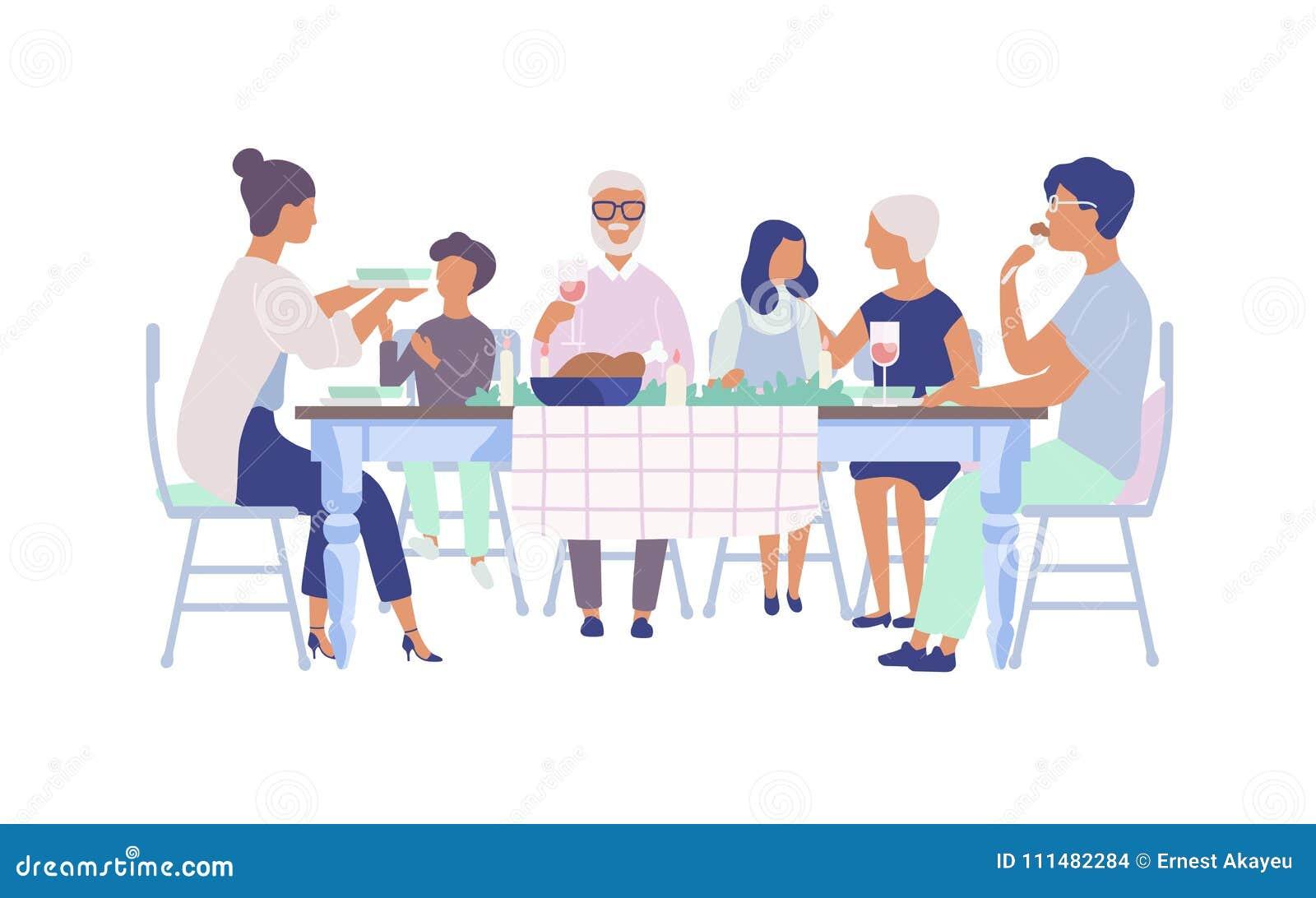 La gente che si siede alla tavola decorata con le candele, mangiando alimento, vino bevente e conversazione l un l altro Festa de