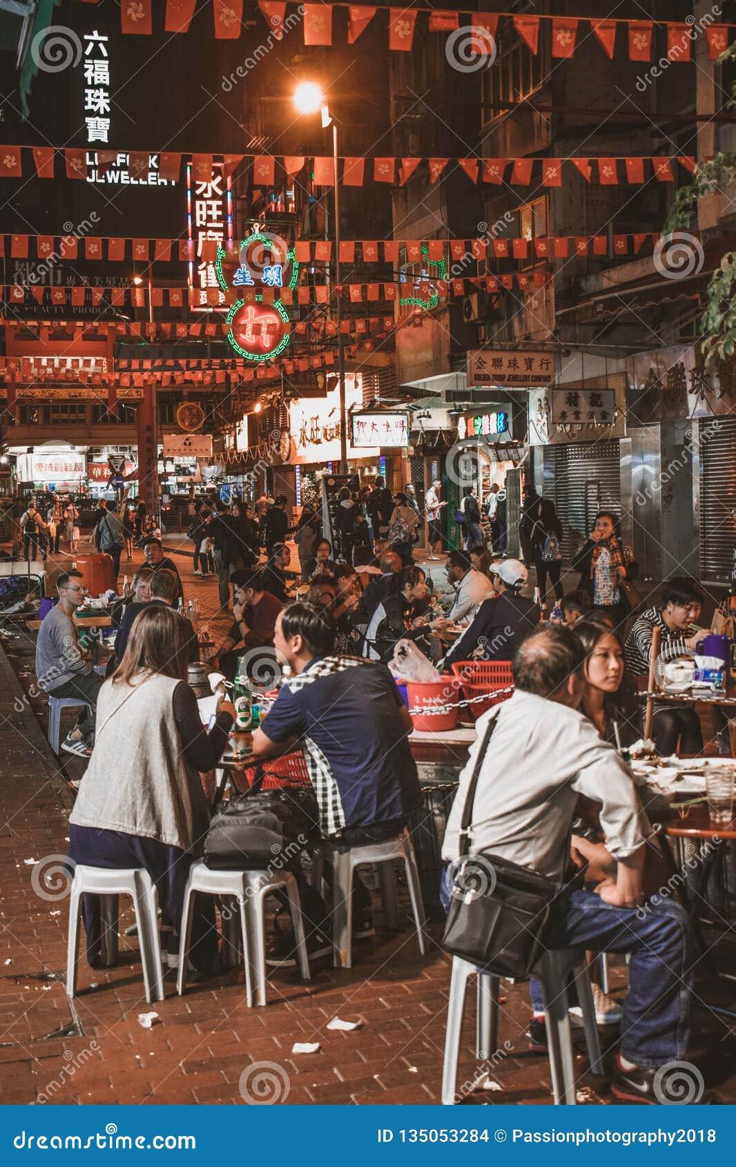 La gente che si siede e che mangia l alimento della via al mercato di strada uguagliante del tempio in Hong Kong