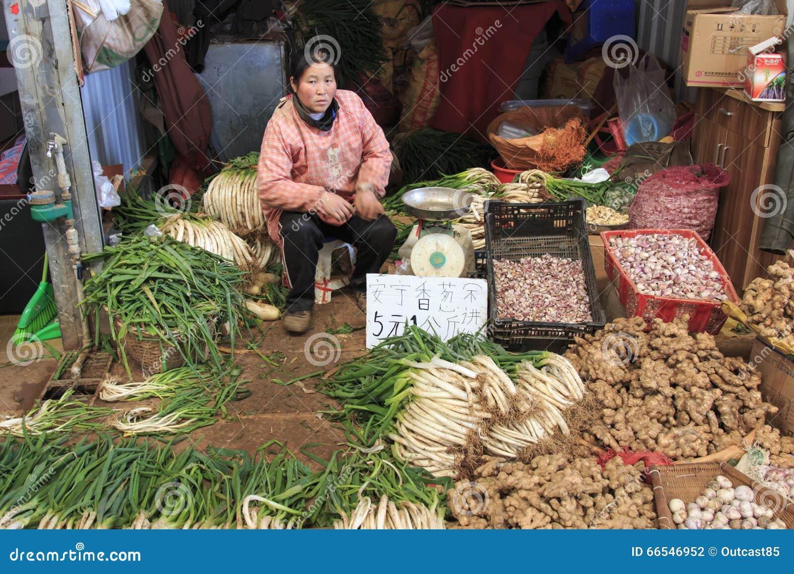 La gente che vende e che compra in un mercato tradizionale del centro di Kunming