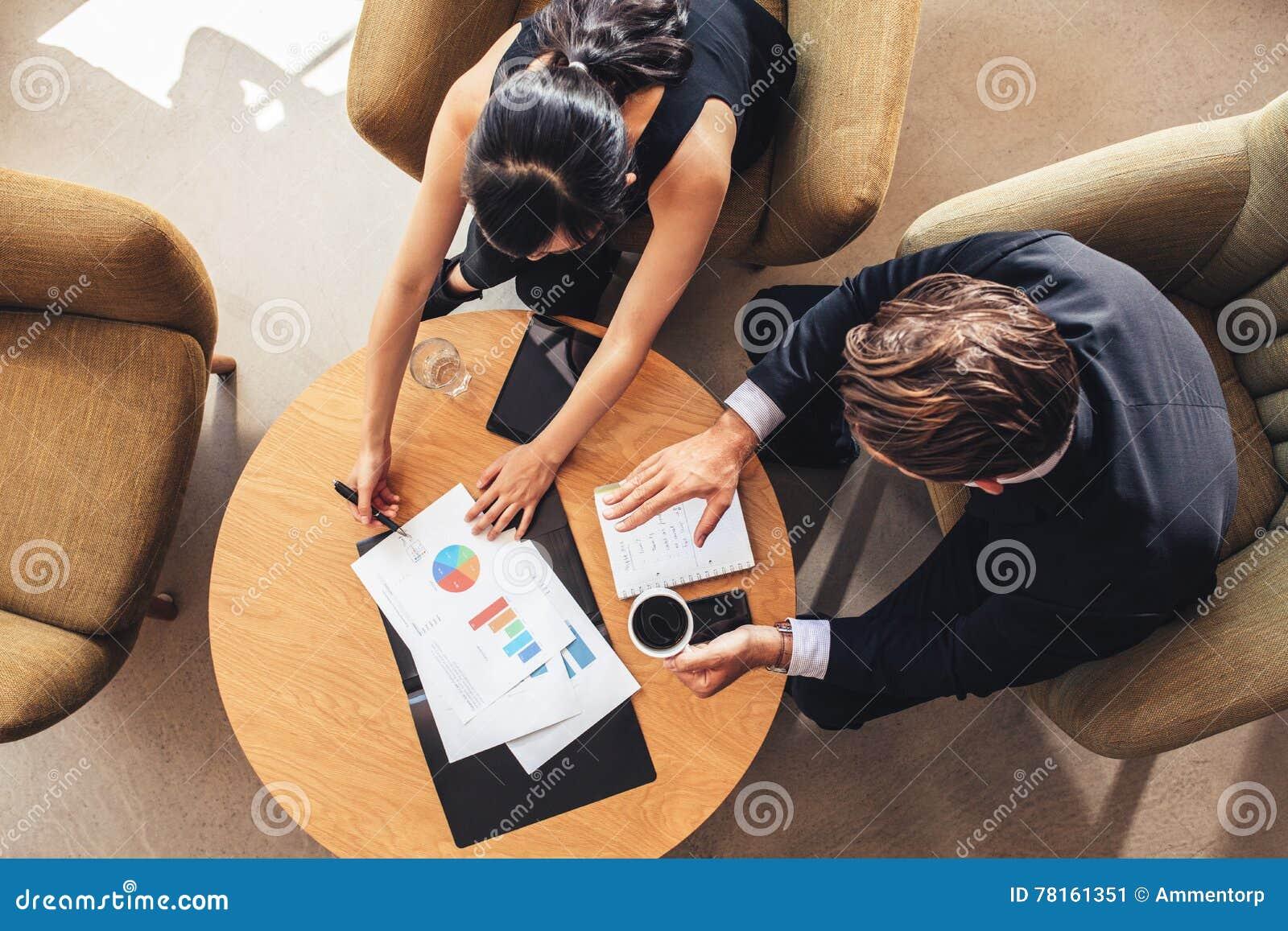 La gente corporativa que discute nuevo negocio proyecta con cartas