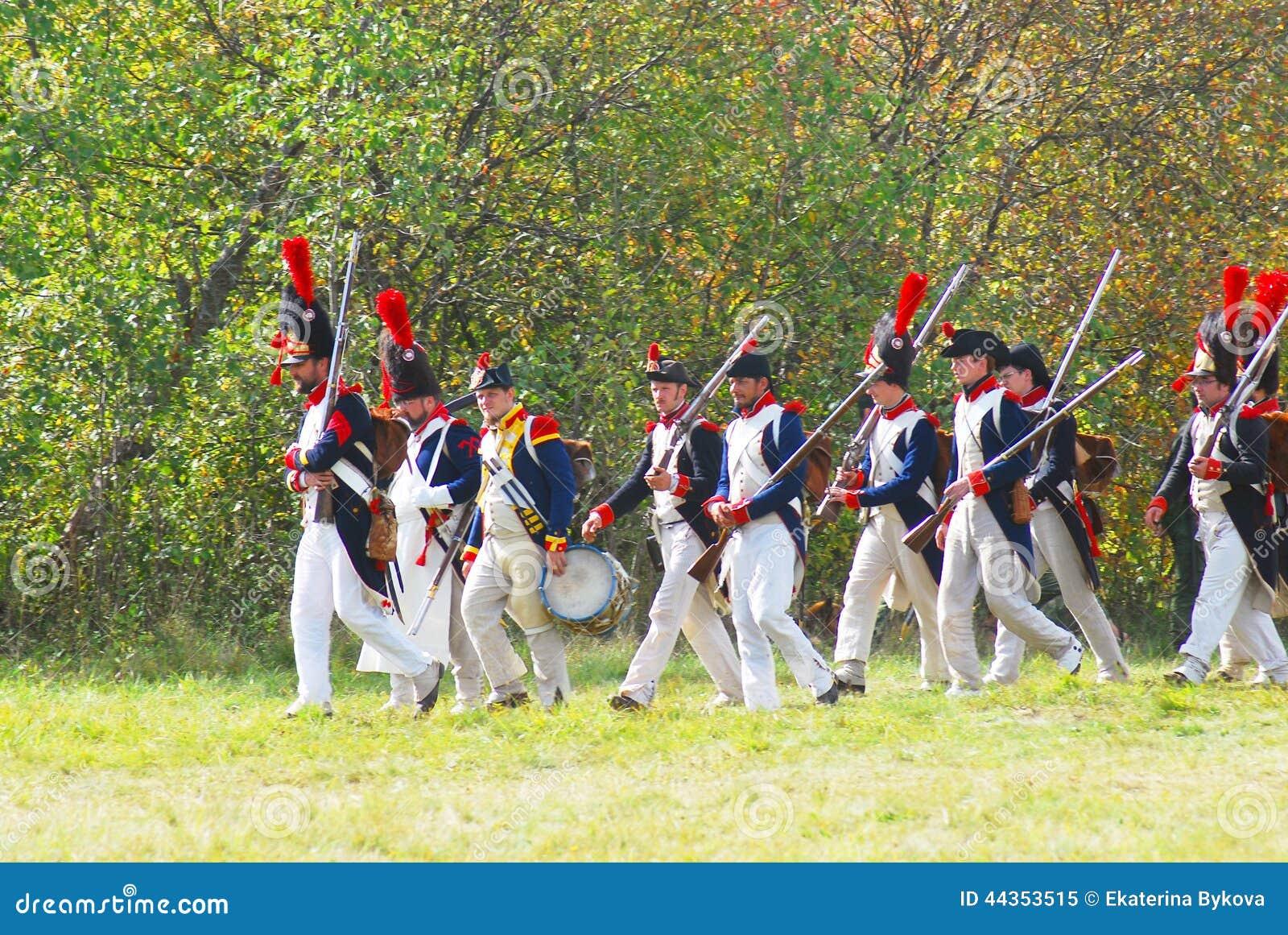 La gente in costumi storici marcia sul campo di battaglia