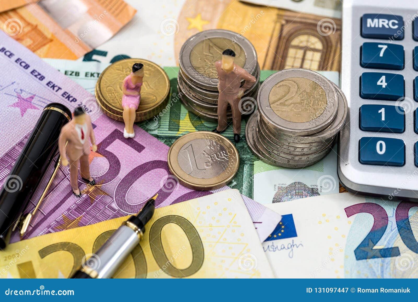 La gente del giocattolo si siede sull euro moneta con le fatture del calcolatore, della penna e dell euro
