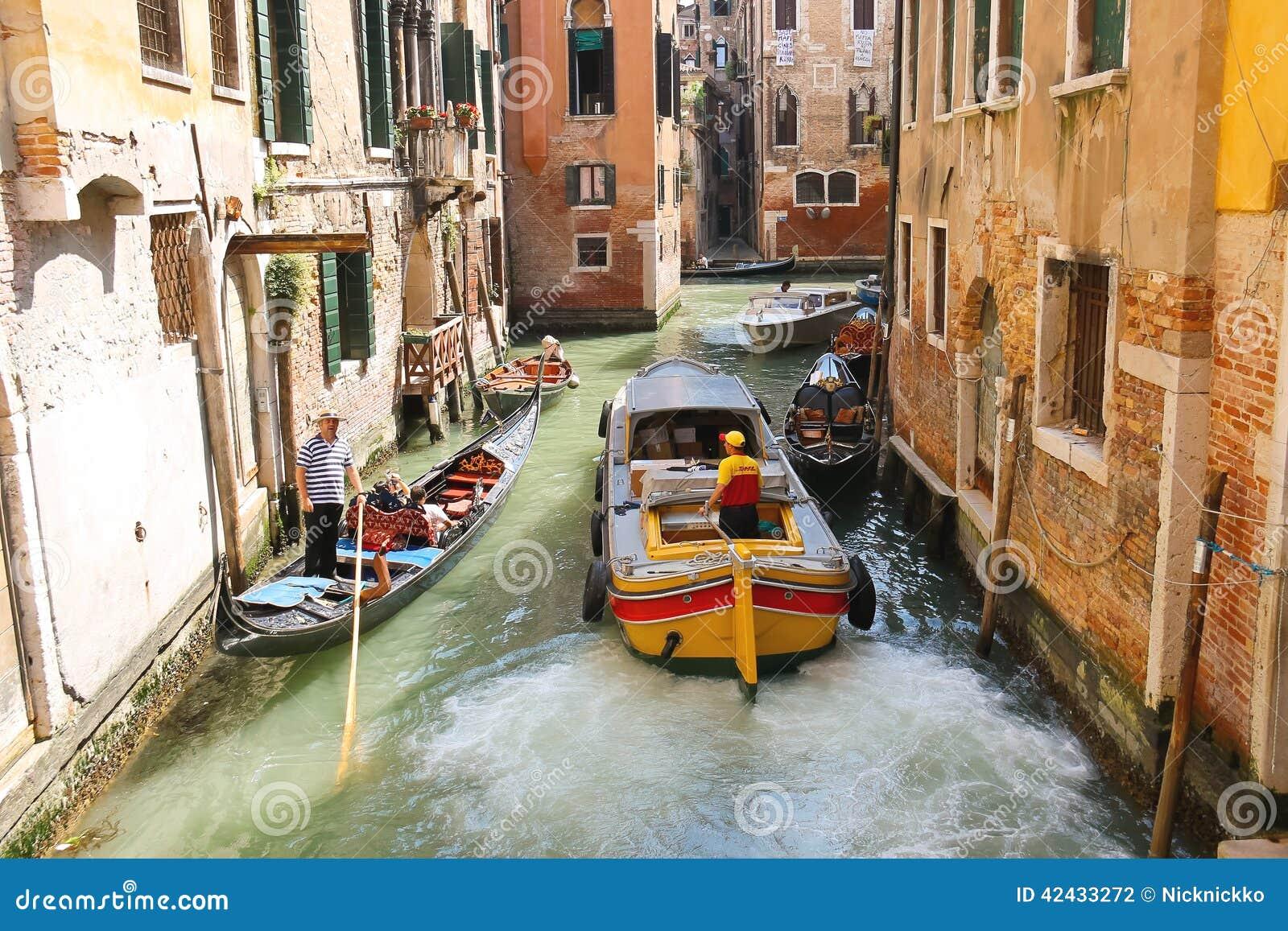 La gente en barcos se mueve a lo largo de un canal en Venecia, Italia
