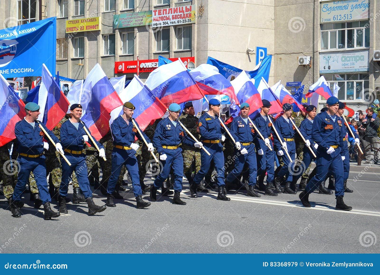 La gente en uniforme con las banderas de la Federación Rusa participa