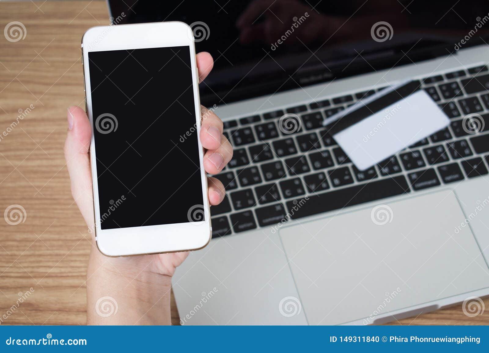 La gente est? utilizando smartphones para pagar v?a una tarjeta de cr?dito colocada en un ordenador port?til en una tabla de made